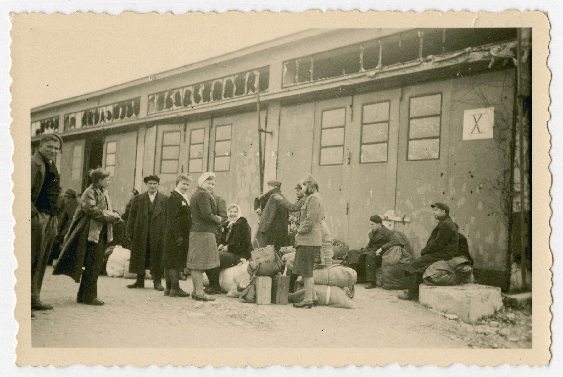 "A group of Buchnewald survivors wait to be transported to another location after the camp was liberated.  The photograph's orginal caption reads, ""They wait for departure. luggage and all and then they all start to...."""
