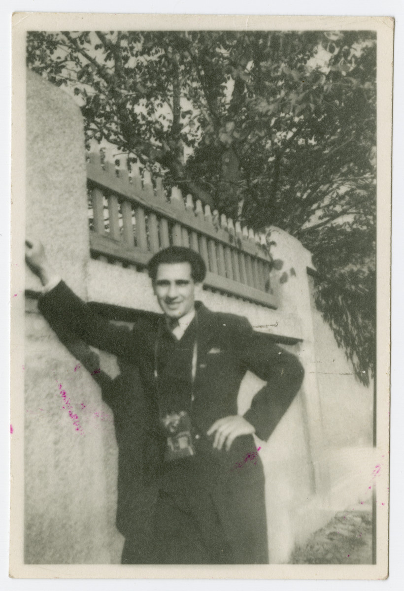 Robert Wilonsky stands next to a wall with a camera around his neck.