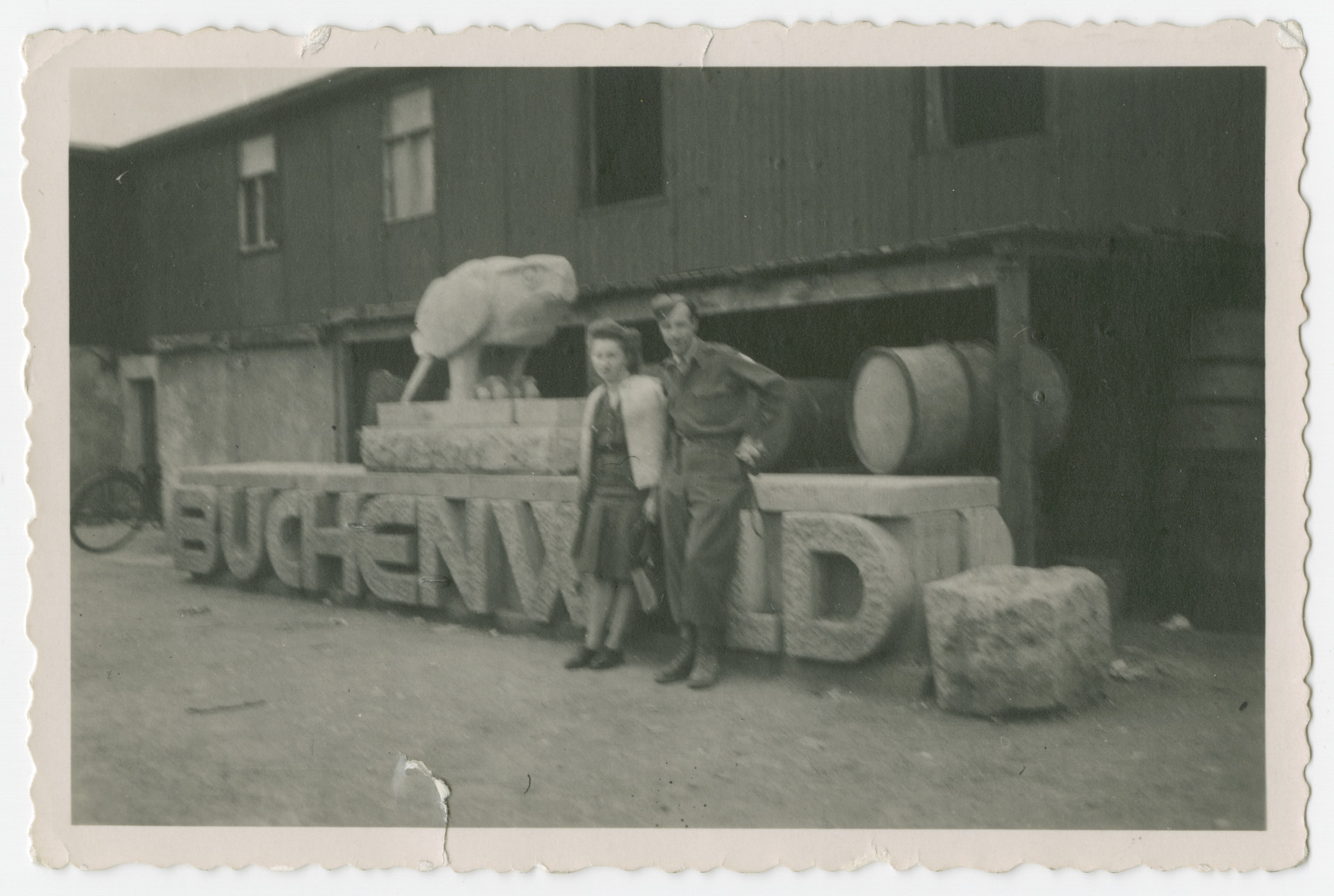 """A soldier and a young woman stand in front of the Buchenwald Concentration Camp's entrance sign after the camp was liberated.  The photograph's orginal caption reads, """"These are not my own snap shots, Honey and they are a part of Usn's only because I have set foot on all terra firma in these snaps. This is Buchenwald - the crude entrance - huh?"""""""