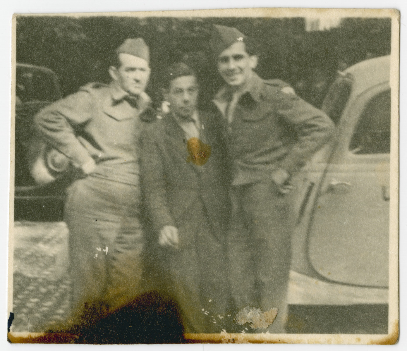 Three men pose beside an automobile in postwar Munich.  On the right is Robert Wilonsky who worked for the Joint Distribution Committee.