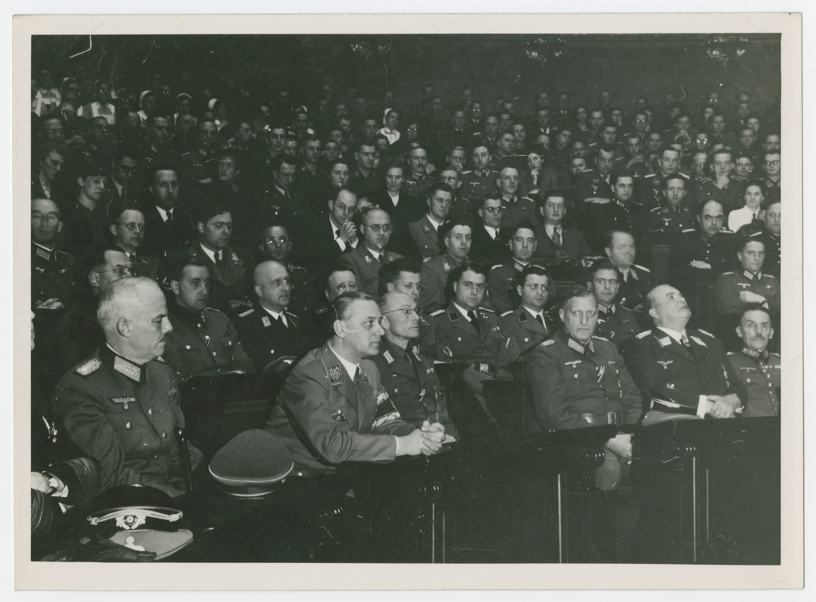 Alfred Rosenberg sits in the French National Assembly where he is giving a major address.  Among those pictured are:  Helmuth Knochen (Commander of the secret police in occupied Paris), Hugo Sperrle (Luftwaffe general), and Otto Von Stulpnagel (Military commander of France).  The following have also been identified:  third from right:  SS-Brigadefuehrer Dr. Harald Turner (in German Army administration official uniform in his capacity as Chief of the German Military Administration in Paris), and at far left in the foreground:  SA-Obergruppenfuehrer Friedrich (Fritz) Pfeffer von Salomon (in the uniform of a Kriegsverwaltungsvizechef), who served from October 25, 1940 to March 1, 1941 as Deputy Chief of the Administrative Staff to the Military Commander in France.
