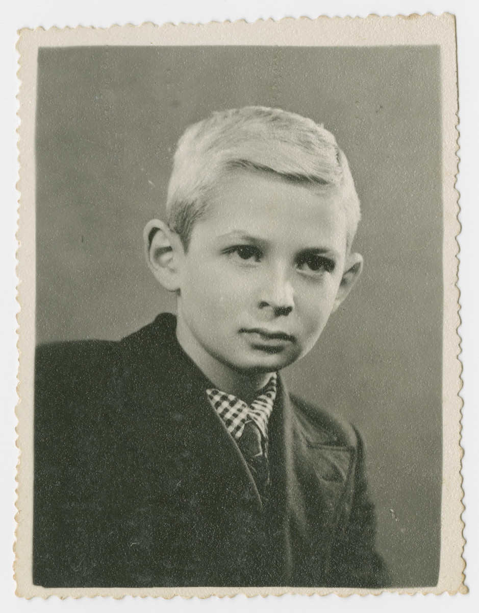 Studio portrait of Jerzy Ogurek taken after his family fled to Hungary.  His mother had dyed his hair blond so that he would look less Jewish.