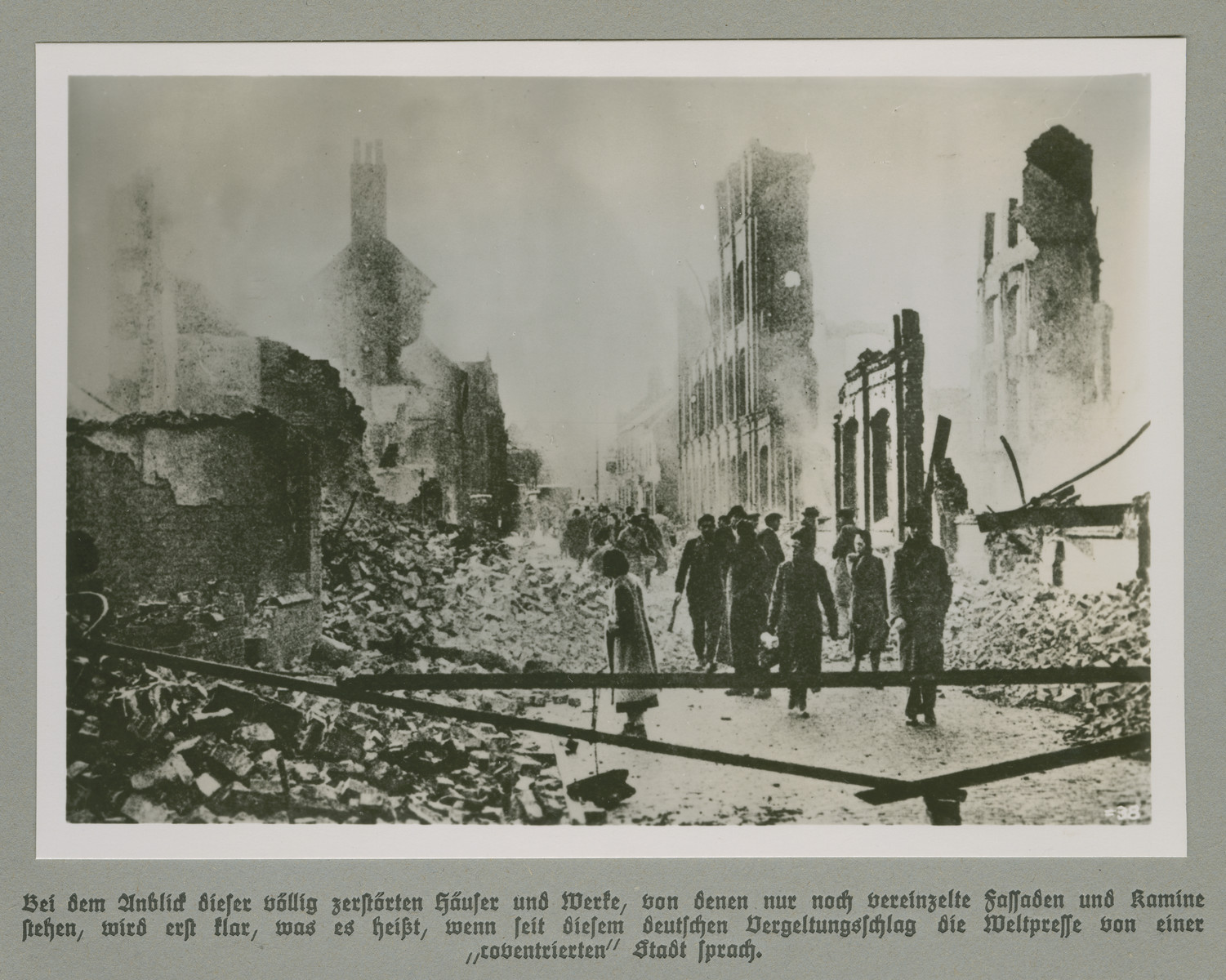 "Men and women walk through a city quarter reduced to rubble.    Original caption reads: Upon sight of the completely destroyed houses and industrial plants it first becomes clear what it meant, when since the begining of this German retaliation, the global press has spoken of a ""coventried"" (razed) city."