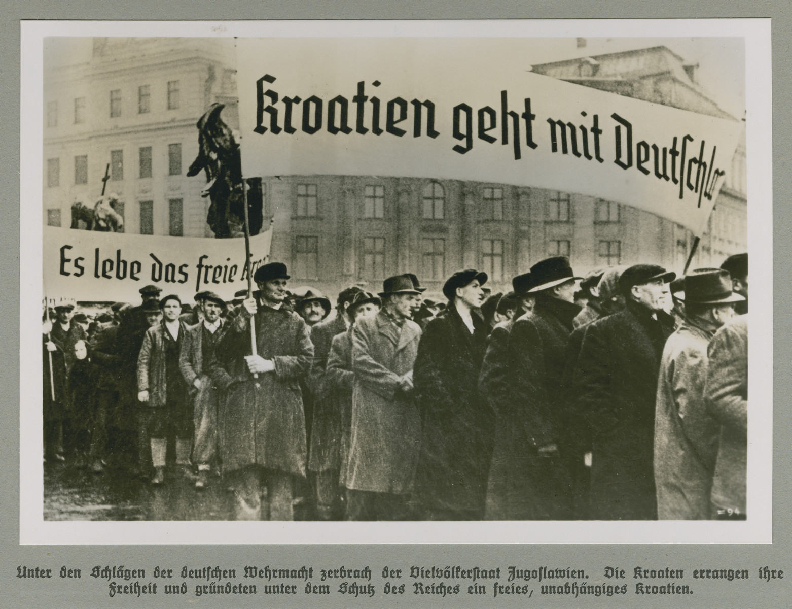 Men march through a city street holding banners celebrating Croatian independence.  Original caption reads: The multi-ethnic state of Yugoslavia broke apart under the blows of the German Wehrmacht. The Croatians won their freedom and founded a free and independent Croatia under the protection of the Reich.