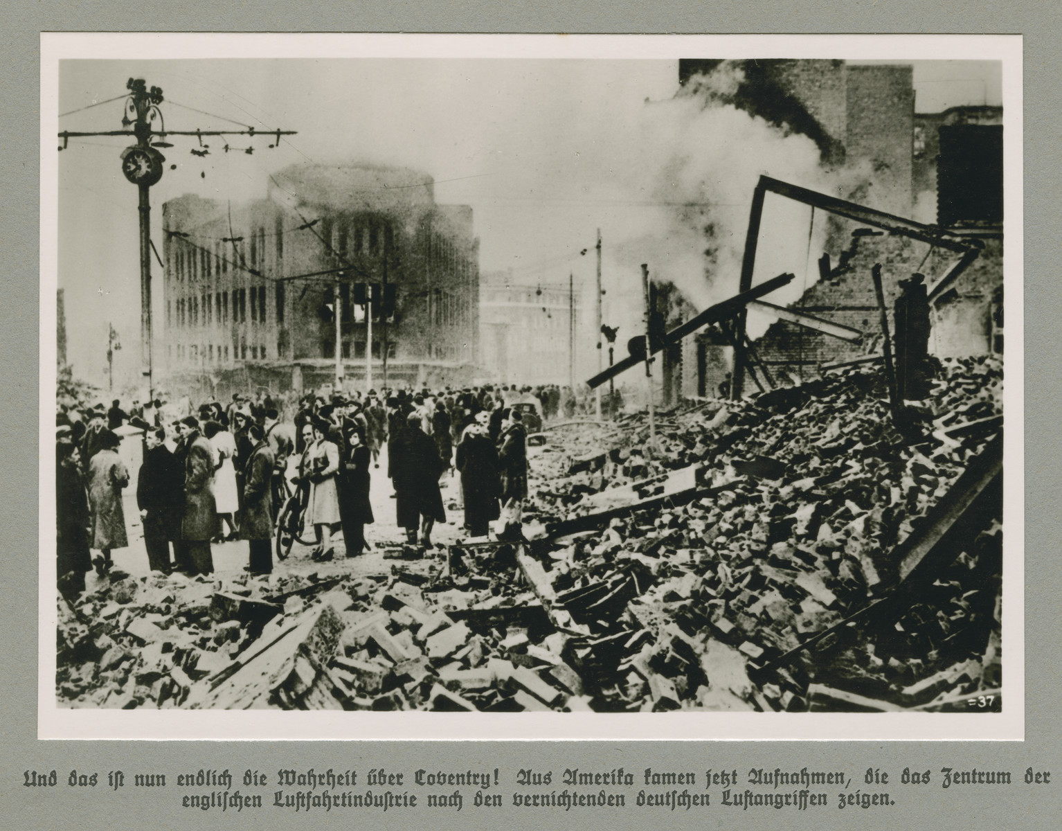 Men and women stand behind piles of rubble in a bombed out city quarter.   Original caption reads: And finally the truth about Coventry! Images have come out of America that depict the center of the English aircraft industry after the devastating German airstrikes.