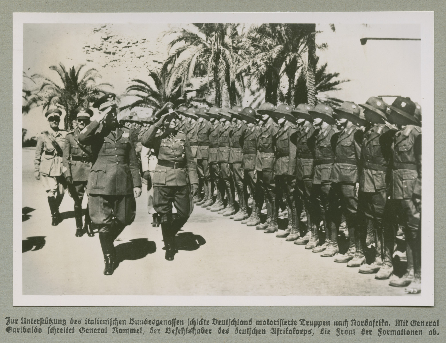 High ranking military personnel walk past and salute troops.  Original caption reads: Germany sent motorized troops to North Africa in support of its Italian allies. General Rommel, the commander of German troops in North Africa, walks with General Garibaldo astride the front line of the formation.
