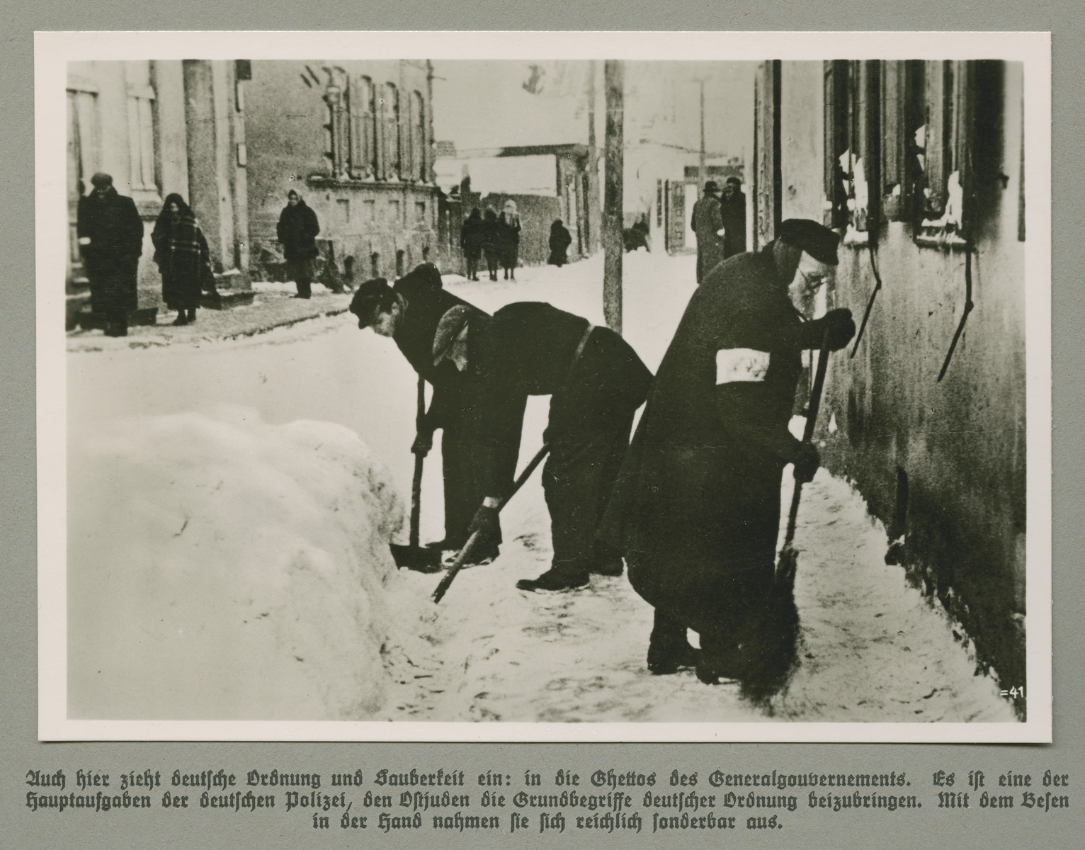 Three men, one with an armband, clear snow in the street of an unidentified ghetto.  Original caption reads: German tidiness and cleanliness settles in here too: in the the ghettos of the Generalgouvernment. It is one of the primary duties of the German police to teach Eastern Jews the basics of German order. They look quite peculiar with a broom in the hand.