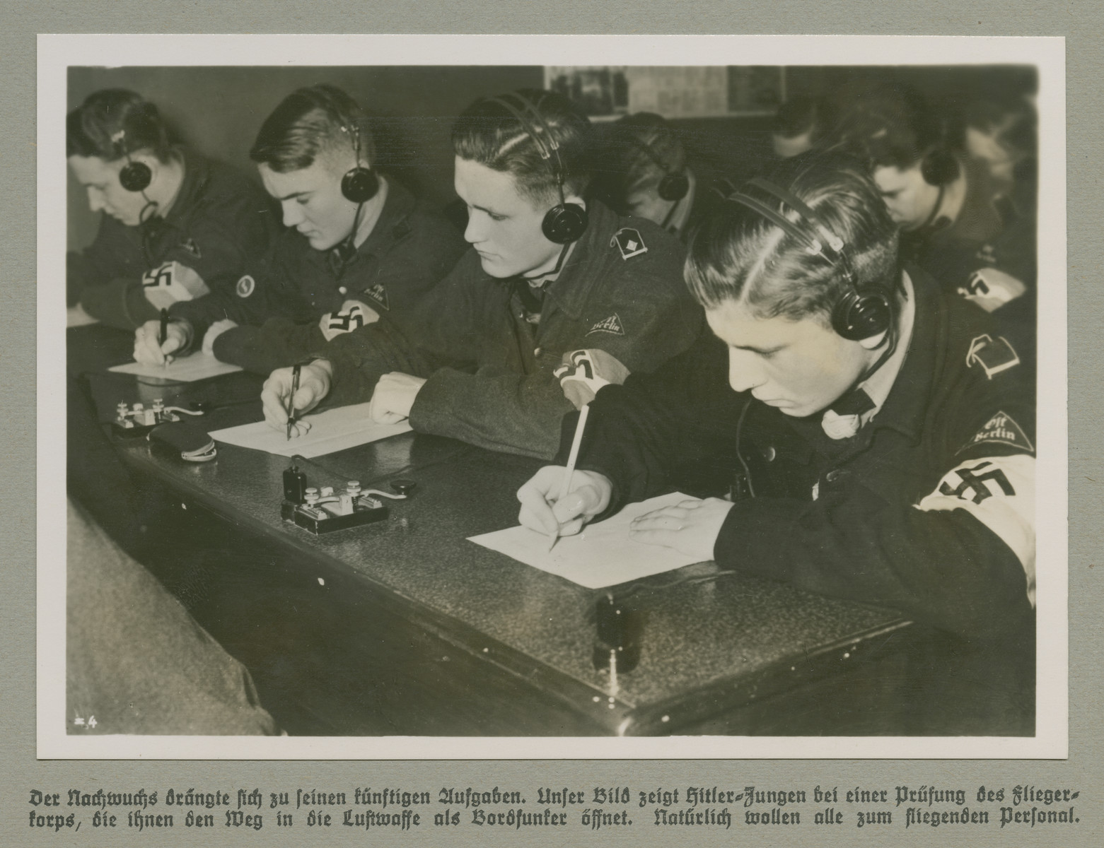 Hitler Youth members are photographed during a radio operator's exam.   Original captions reads: The trainee commits himself to his future responsibilities. Our image depicts Hitler Youths during an Air Corps exam that will clear the path to join the Luftwaffe as a radio operator. Naturally all want to join flying crews.