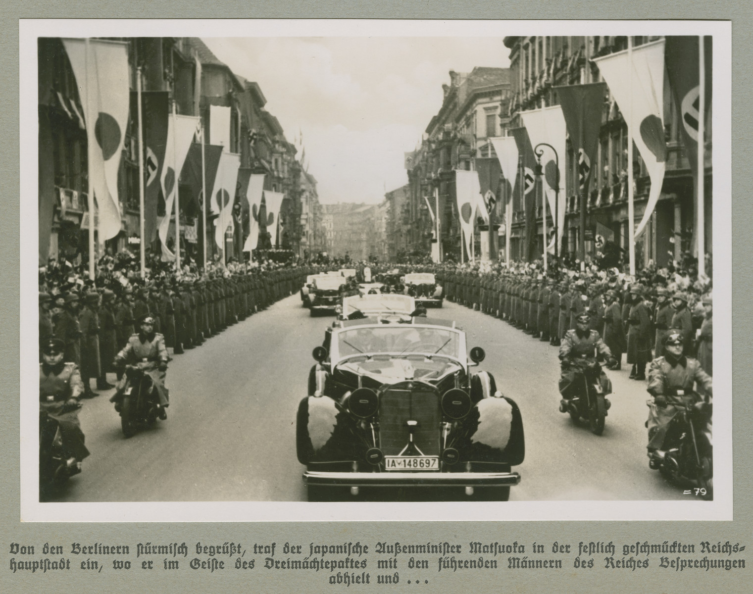 A motorcade proceeds down a Berlin street lined with Japanese and Nazi flags.  The original caption reads:  Welcomed enthusiastically by the people of Berlin, the Japanese Foreign Minister Matsuoka arrives in the festively adorned capital  where he met and held talks with the Reich's leading men as a representative of the Tripartite Pact, and...   (Caption continues with associated image on WS# 75979)