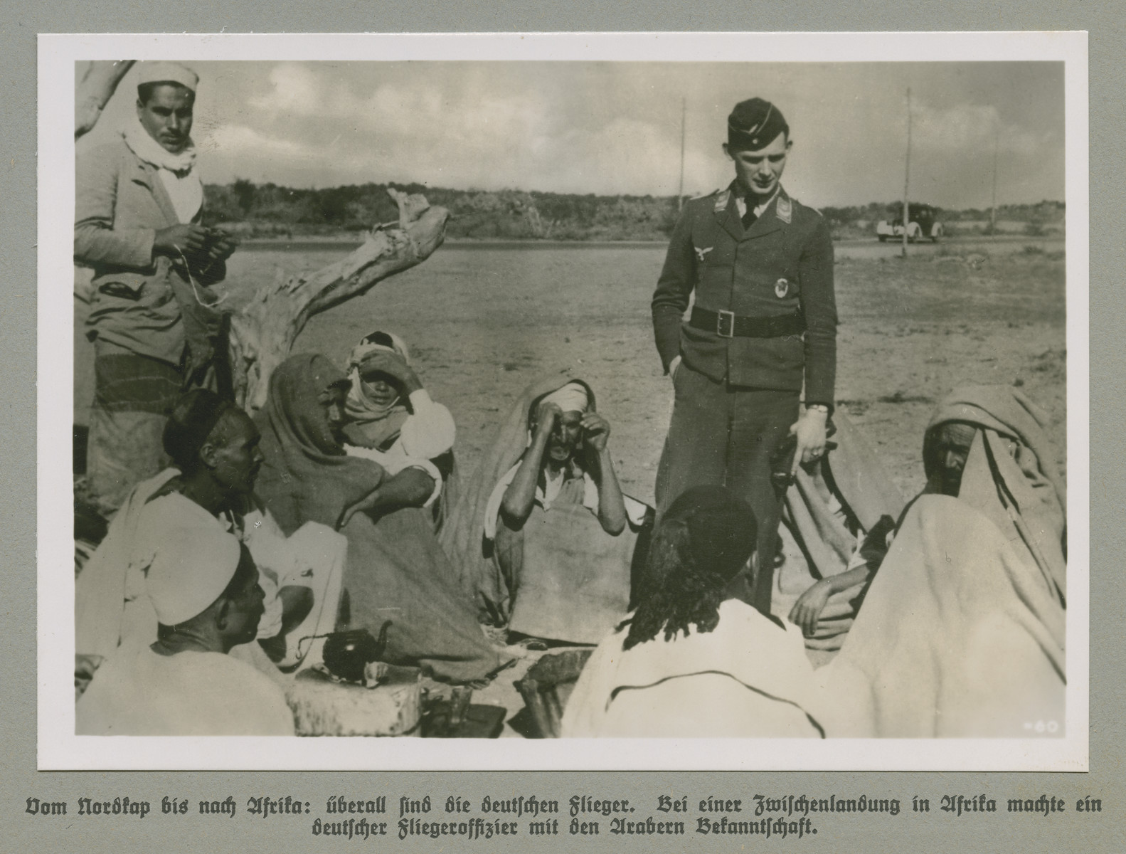 A man in German military uniform stands before a group of Arab men and women.   The original caption reads: From the North Cape all the way to Africa: German airmen are everywhere. A German air force officer makes the acquaintance of Arabs during a stopover in Africa.     Grossdeutschland in Weltgeschehen, Tagesberichte 1941.
