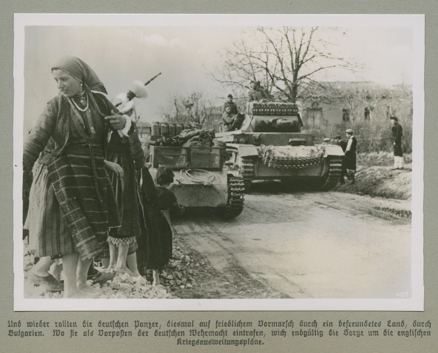 German tanks roll down on a dirt road. while men, women, and children stand offside.    Original caption reads: The German panzers roll by again, this time on a peaceful advance through an allied country, Bulgaria. In Bulgaria they arrived as outposts for the German Wehrmacht, evading fear of  English plans to escalate the war,