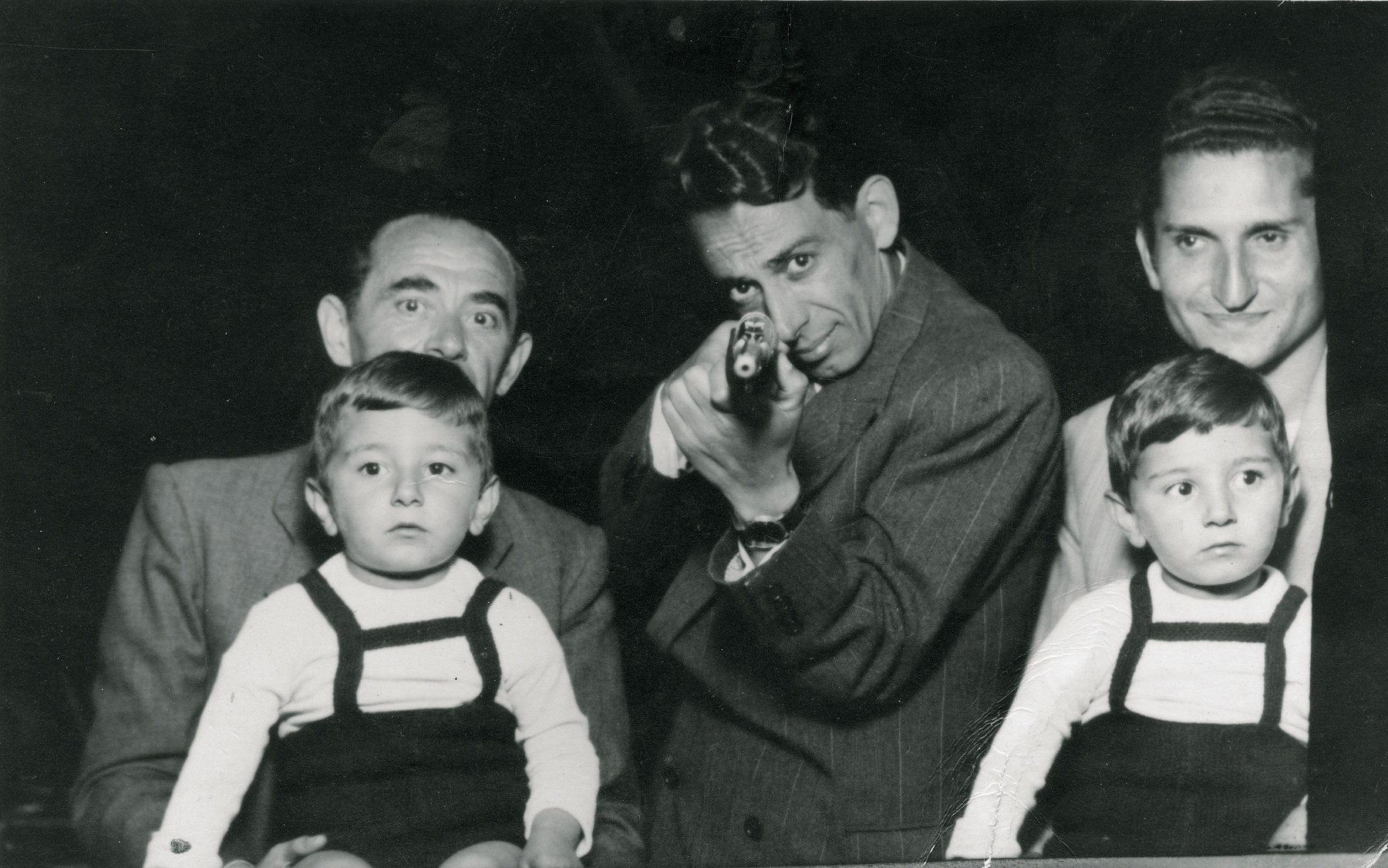 Group portrait of Uncle Chaim Finci, his twin nephews and two other men..   Chaim Finci is in the center pointing a gun at the camera., the twins, Shmuel and Avraham are on the laps of the other two men.