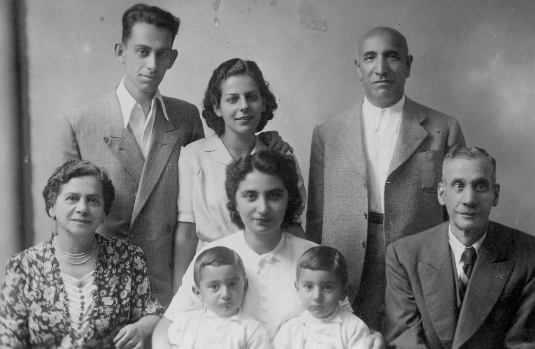 Group portrait of an extended Jewish family who fled to Italy.  Pictured in the back row from left to right: Chaim Finci, Tilda (Finci) Mosafia, and Albert Kabilio. Pictured in the front row from left to right: Rahel Finci, Ella (Kabilio) Finci with her sons, Shmuel and Avraham, in her hands, and Avram Finci.