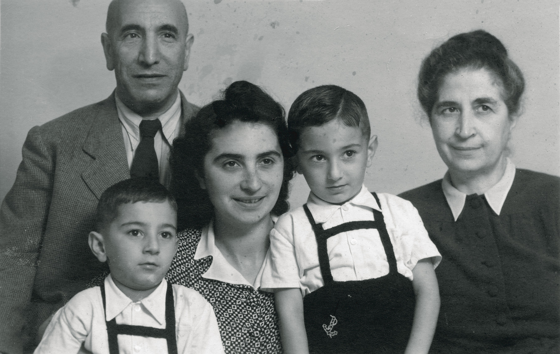 Studio portrait of the Kabillo Finci family.  Pictured are Ella (Kabilio) Finci, her twin sons, Shmuel and Avraham Finci, and her parents, Albert and Blanka Kabilio.