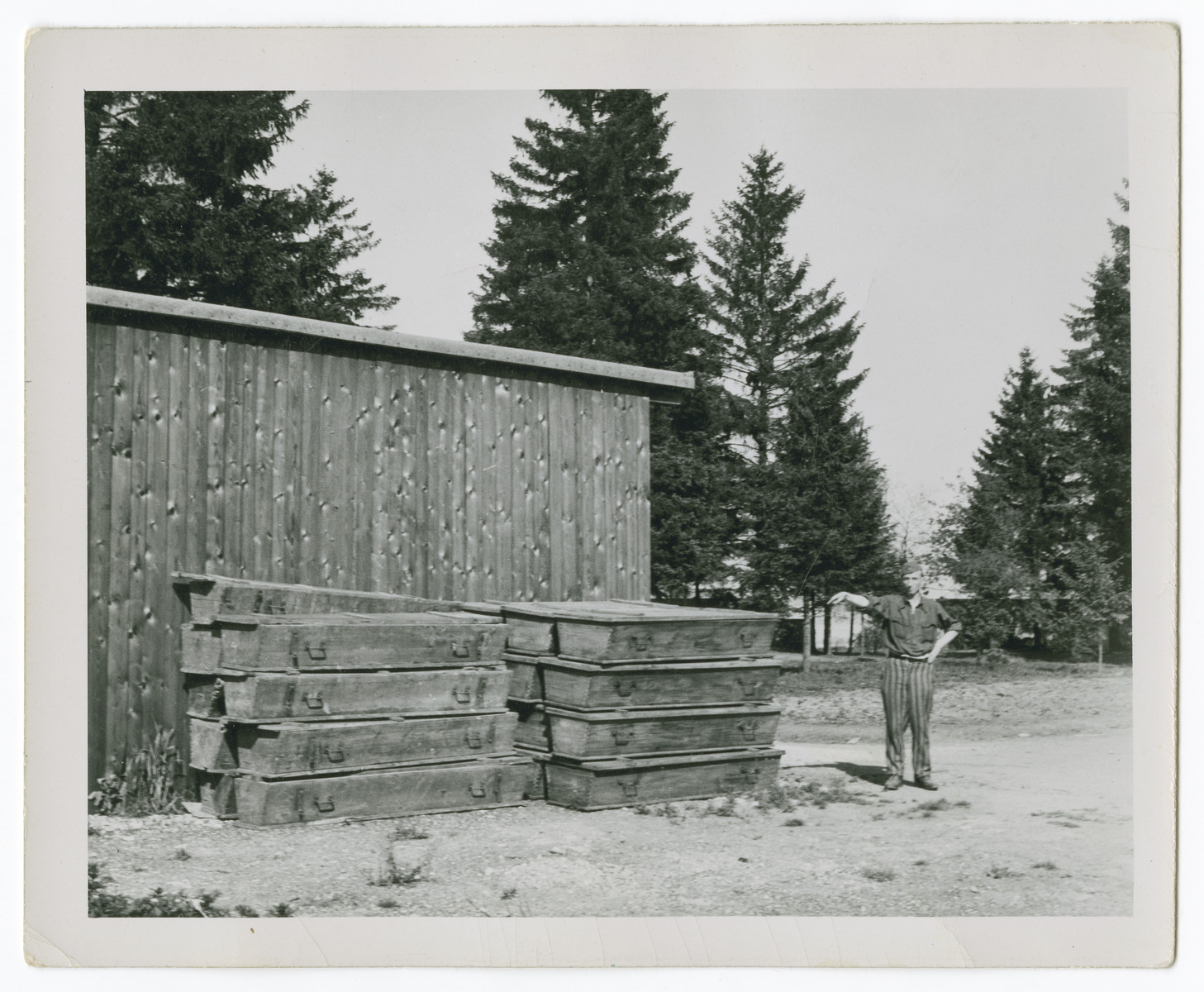 A liberated prisoner stands next to a stack of coffins outside a barrack of the Dachau concentration camp.