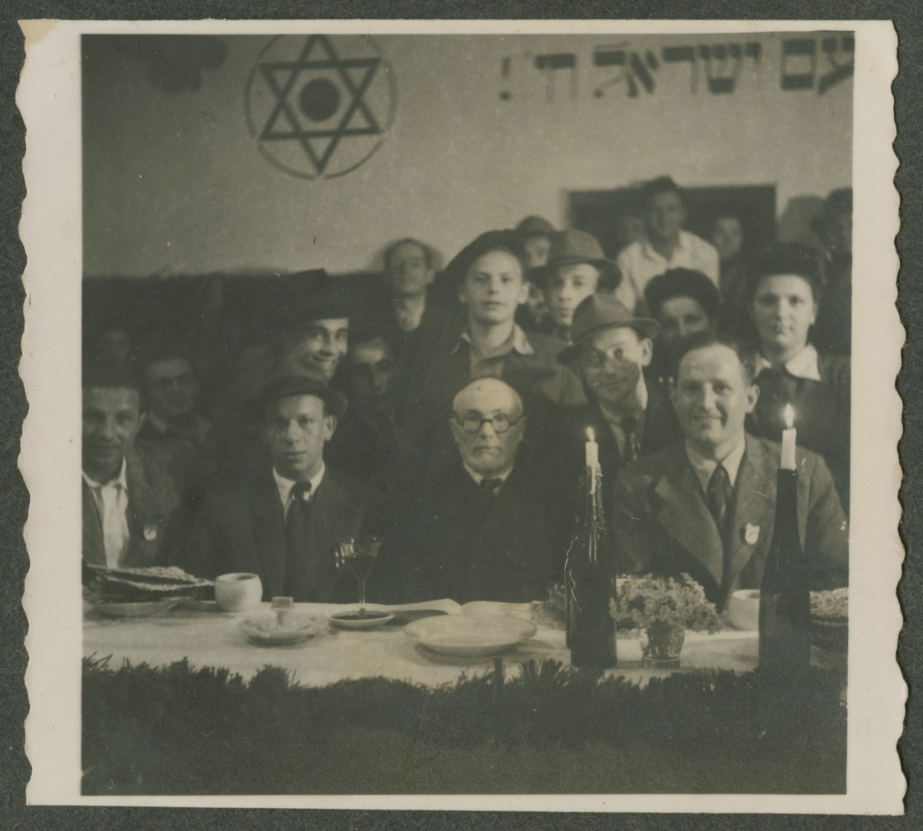 """A group of Jewish displaced persons enjoys their first Passover  since liberation.   The table is set with matzah and wine and the sign on the wall reads """"The nation of Israel lives."""""""