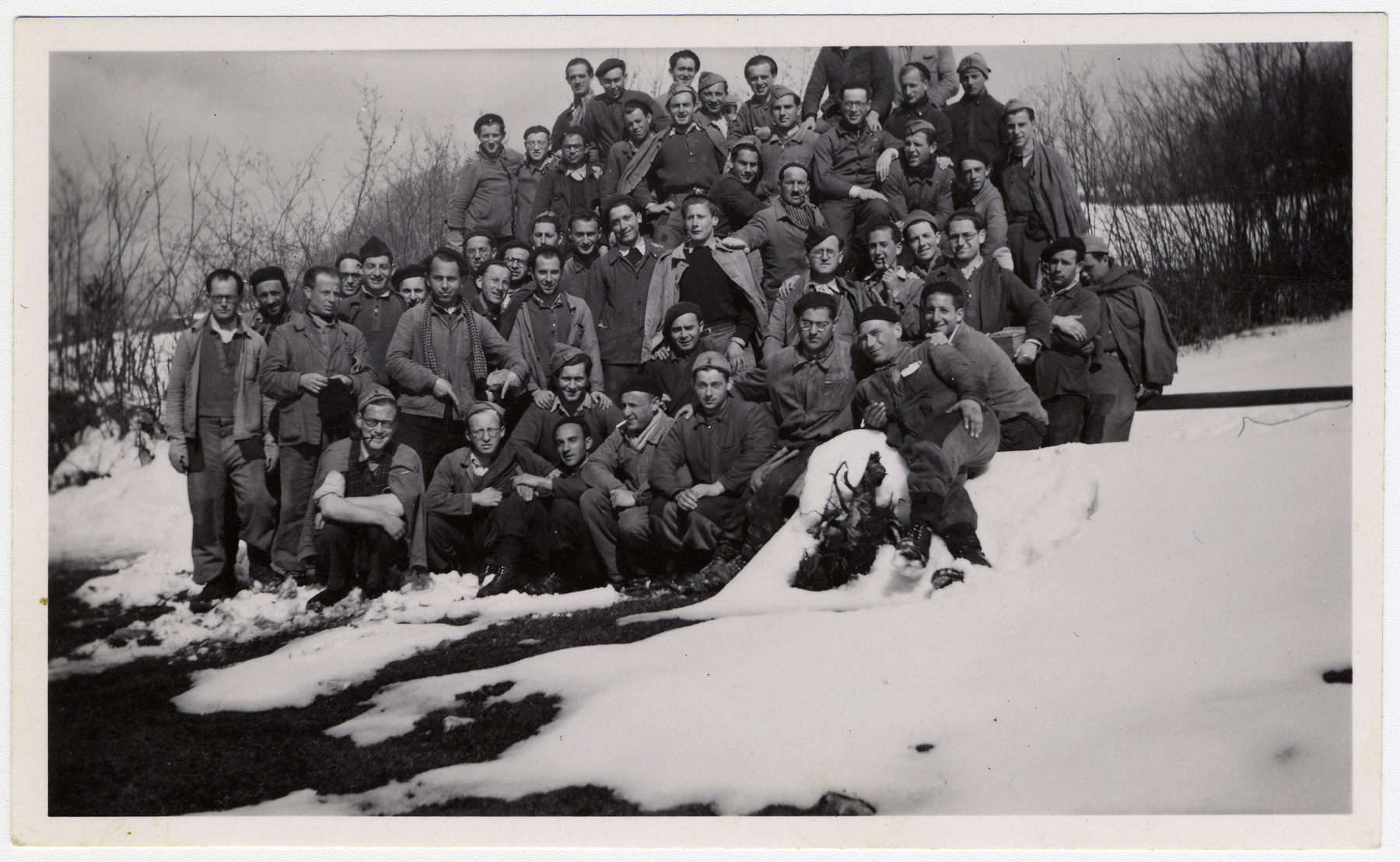 Group portrait of Jewish internees posing in the snow in an unidentified Swiss labor camp.  Max Schattner is pictured in the first standing row, second from the left.