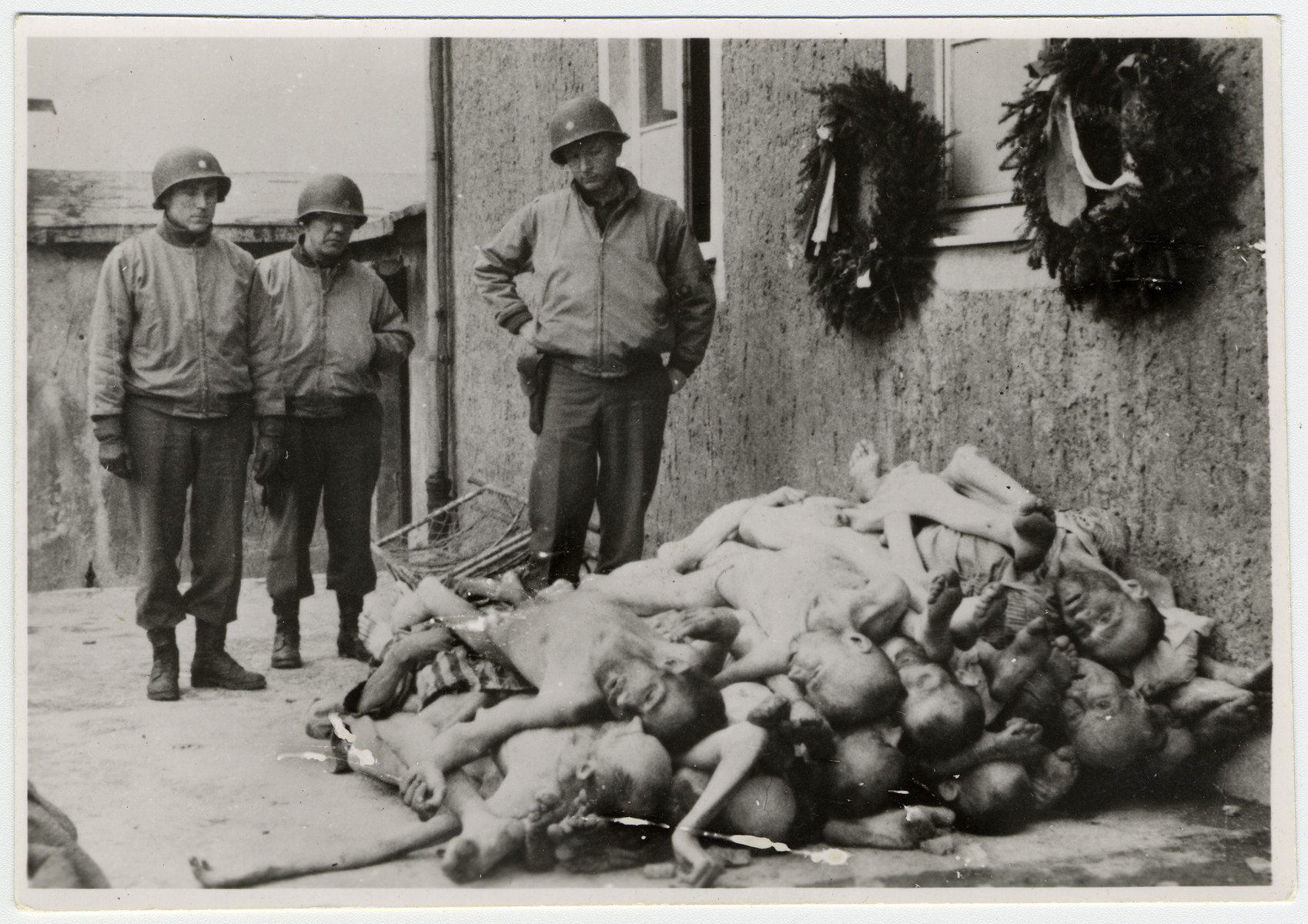 American soldiers view the bodies of emaciated Buchenwald prisoners stacked up next to the crematoria.