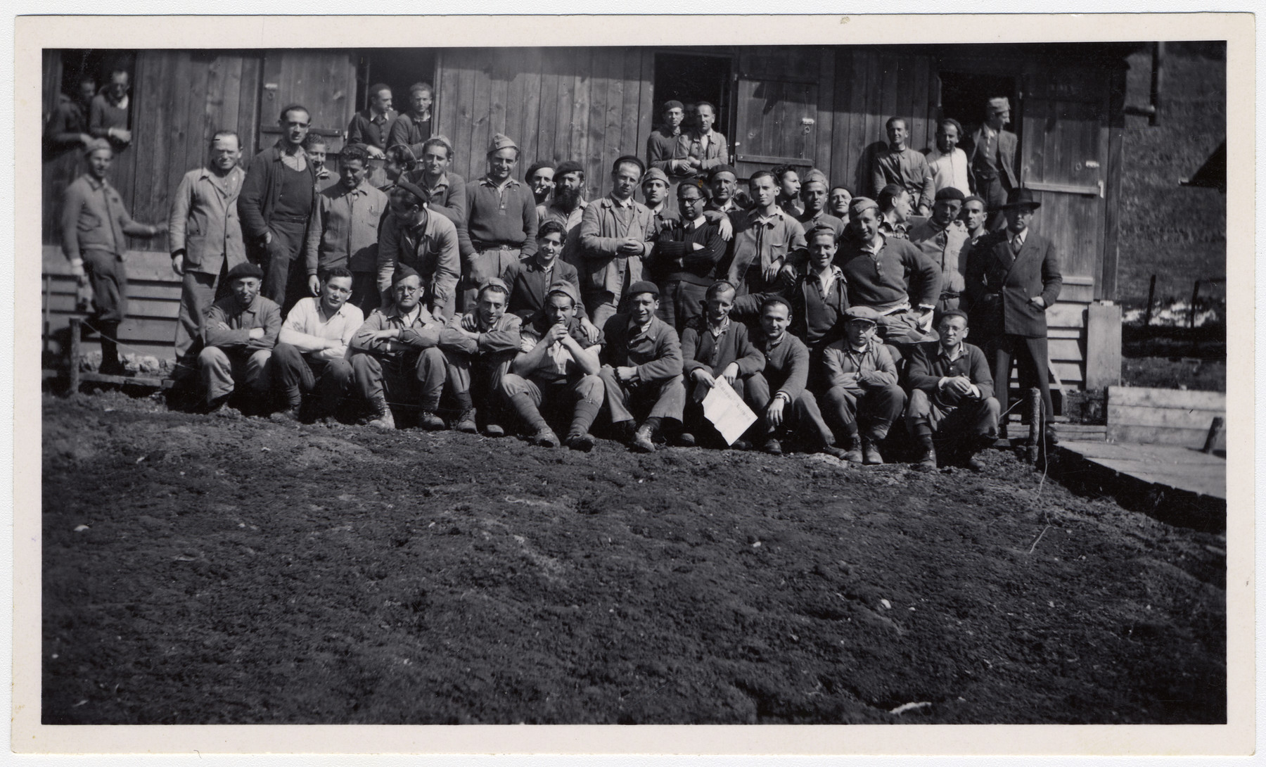 Group portrait of Jewish internees in an unidentified Swiss labor camp.  Max Schattner is standing in the middle with a black cap and light jacket, clasping his hands in front of his chest.
