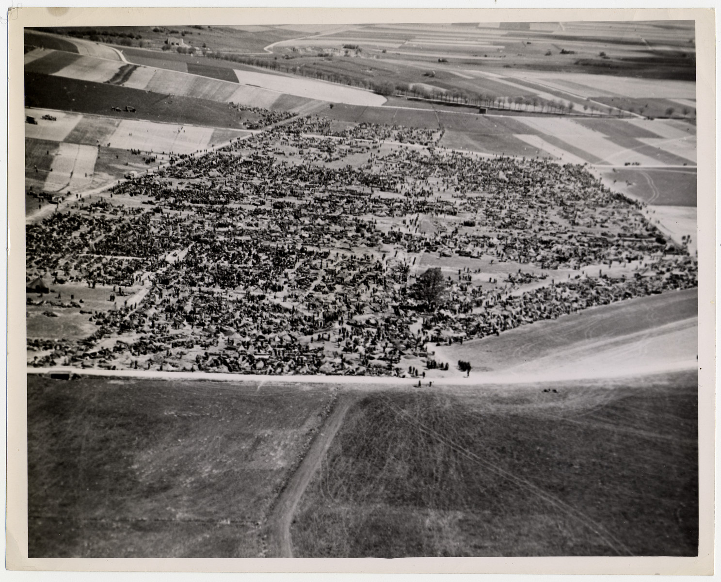 "Aerial photograph of an American Army prisoner-of-war camp in Brilon, Germany.  Original caption reads: ""The camp, 75 miles northeast of the Rhine River city of Cologne, holds some of the 316,930 Nazi troops captured in the Ruhr pocket by American forces. It was announced April 22 that a total of 2,260,156 prisoners had been taken by the Allies on the Western Front since ""D-Day"" (June 6, 1944).""  U.S. Signal Corps photo ETO-HQ-45-33419"