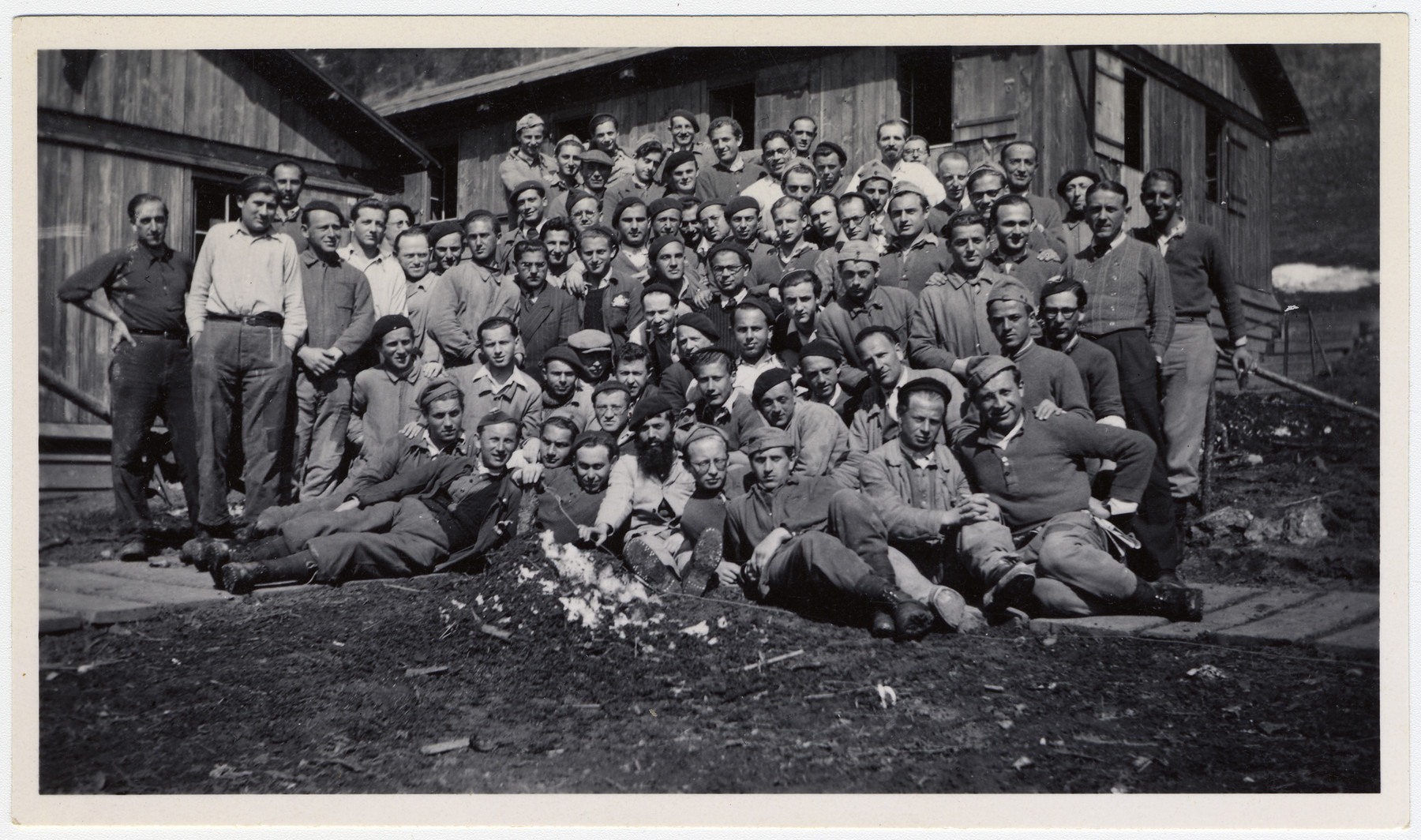 Group portrait of Jewish internees in an unidentified Swiss labor camp.  Max Schattner is pictured in the front row, second from the right with his hands clasped around his knees.