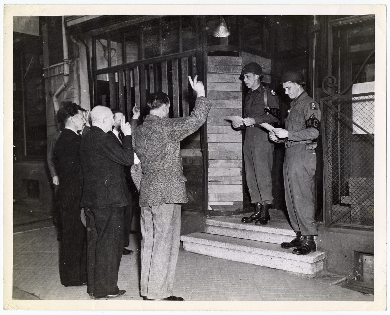 American troops swear in new German civil police.  Pictured are Lieutenant General N.R.S. Thompson of Newton Center, Massachusetts (left) senior military government officer in Herzogenrath, Germany.  (Herzogenrath is five miles north of Aachen on the Dutch frontier.)  U.S. Signal Corps photo ETO-HQ-45-32480