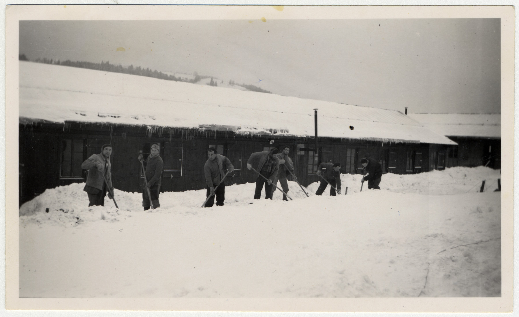 Jewish internees shovel snow in front of the barracks of an unidentified Swiss labor camp.