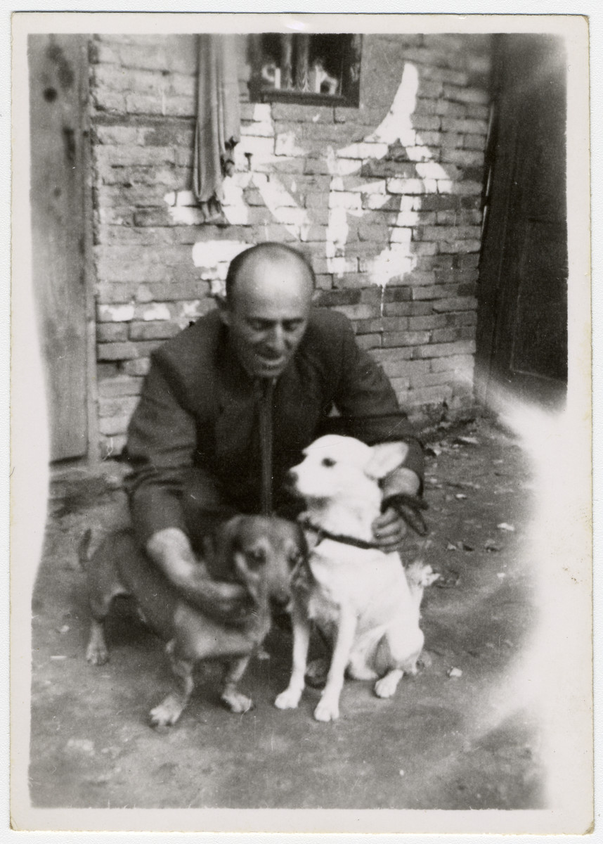 Richard Stock poses with two dogs, Bobby and Jimmy,  outside a building in Shanghai.