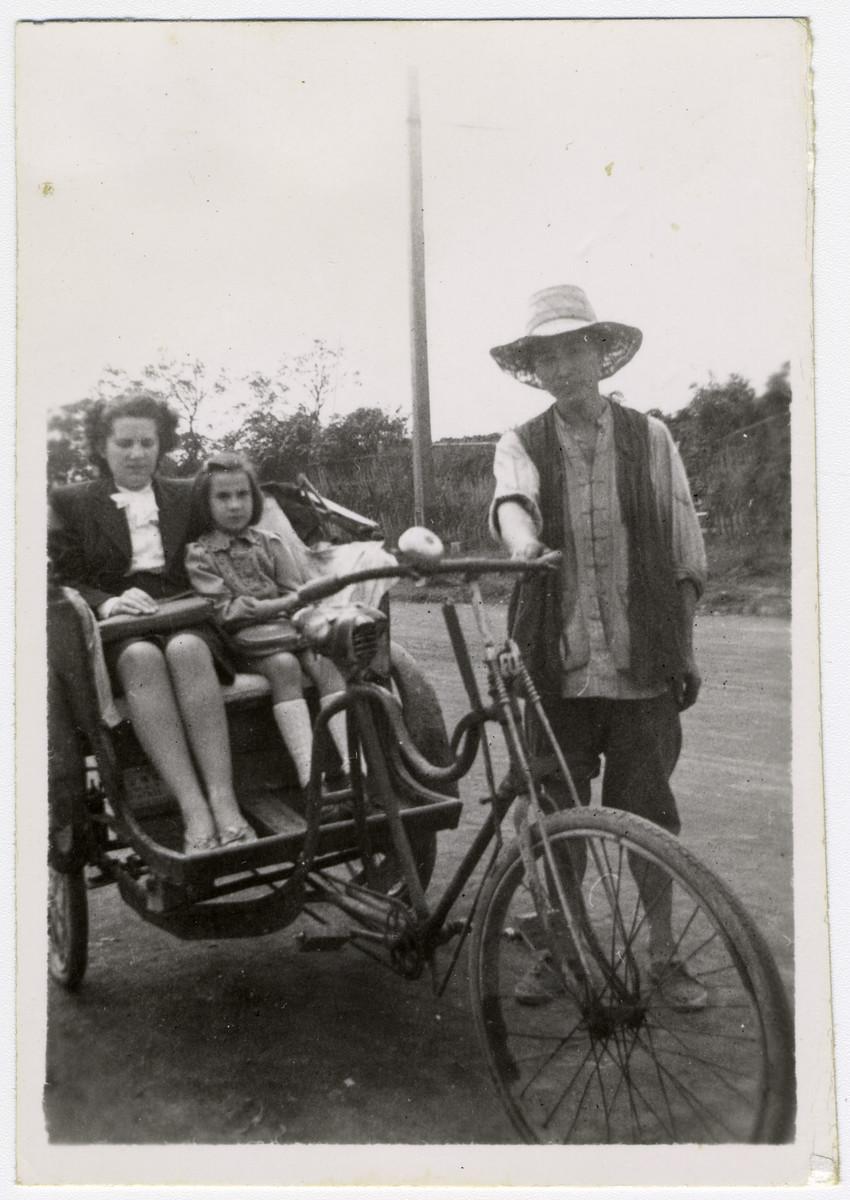 Klara and Helga Schneider take a bicycle powered rickshaw ride in Shanghai.