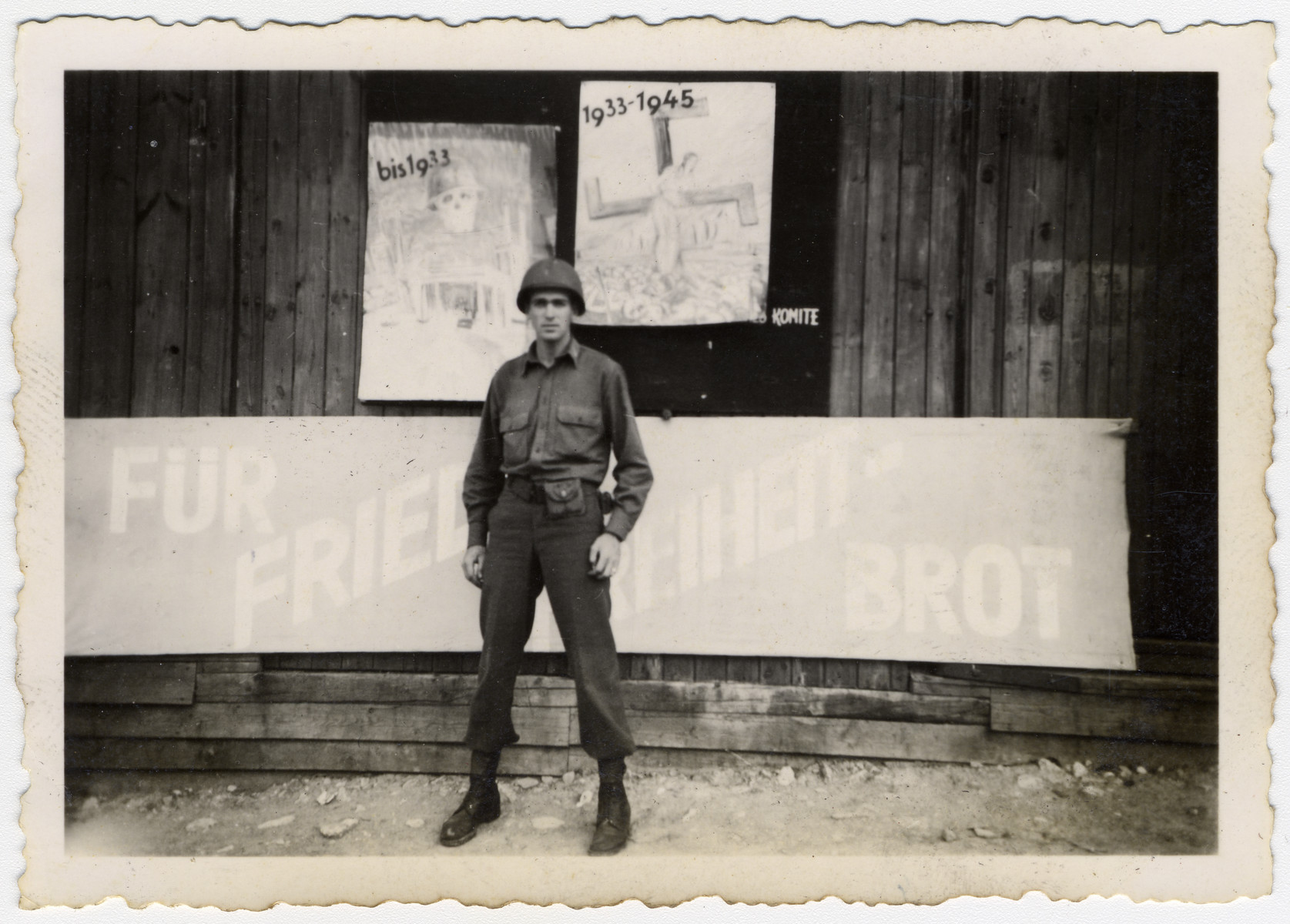 """An American soldier stands in front of a  Buchenwald barrack plastered with anti-Nazi signs.  The caption reads """"Slim Jim"""" [perhaps a nickname of the donor]"""