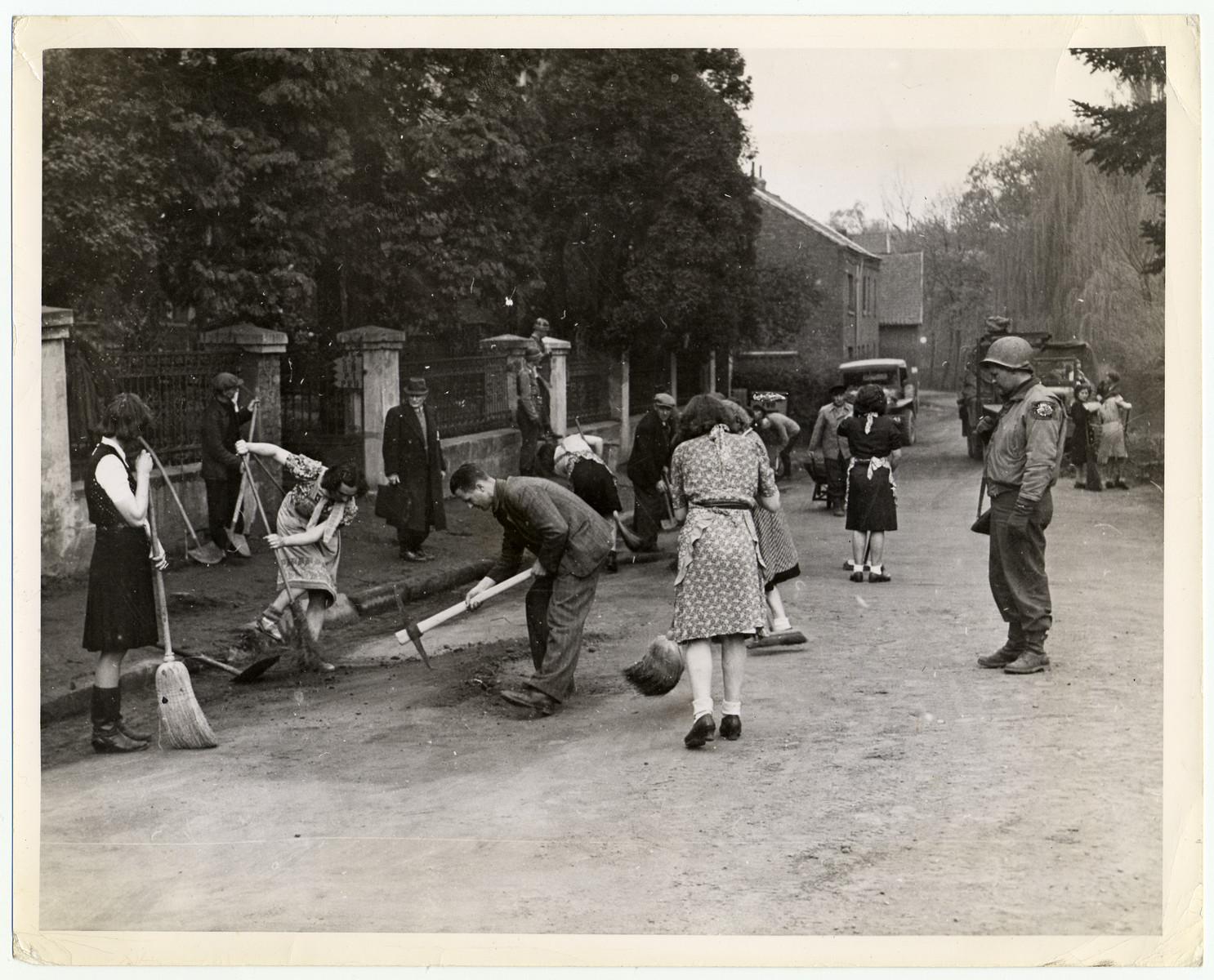 An American soldier supervises German civilians forced to clean the streets of Herzogenrath, Germany, in compliance with orders issued by the Military Government of the town.   Herzogenrath is five miles north of Aachen on the Dutch frontier.   U.S. Signal Corps photo ETO-HQ-45-32490