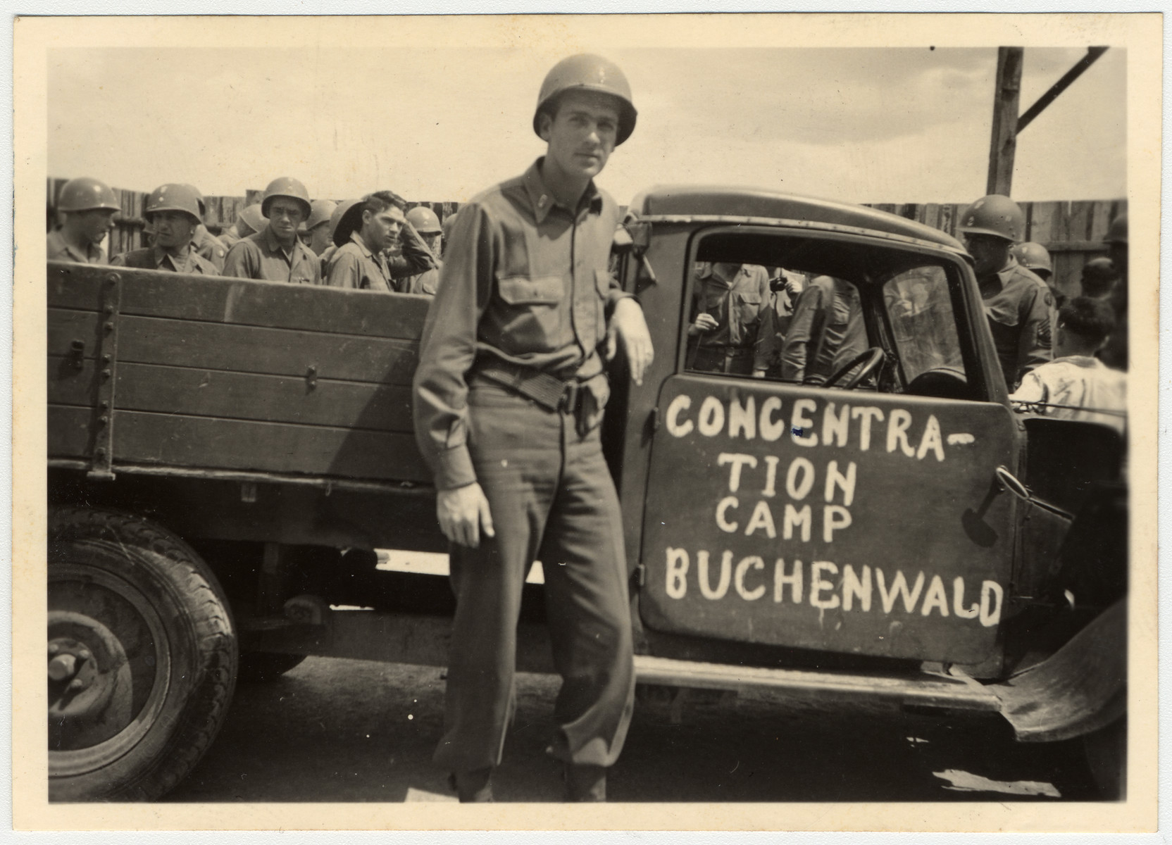 """An American soldier stands in front of a truck labeled """"Concentration Camp Buchenwald."""""""