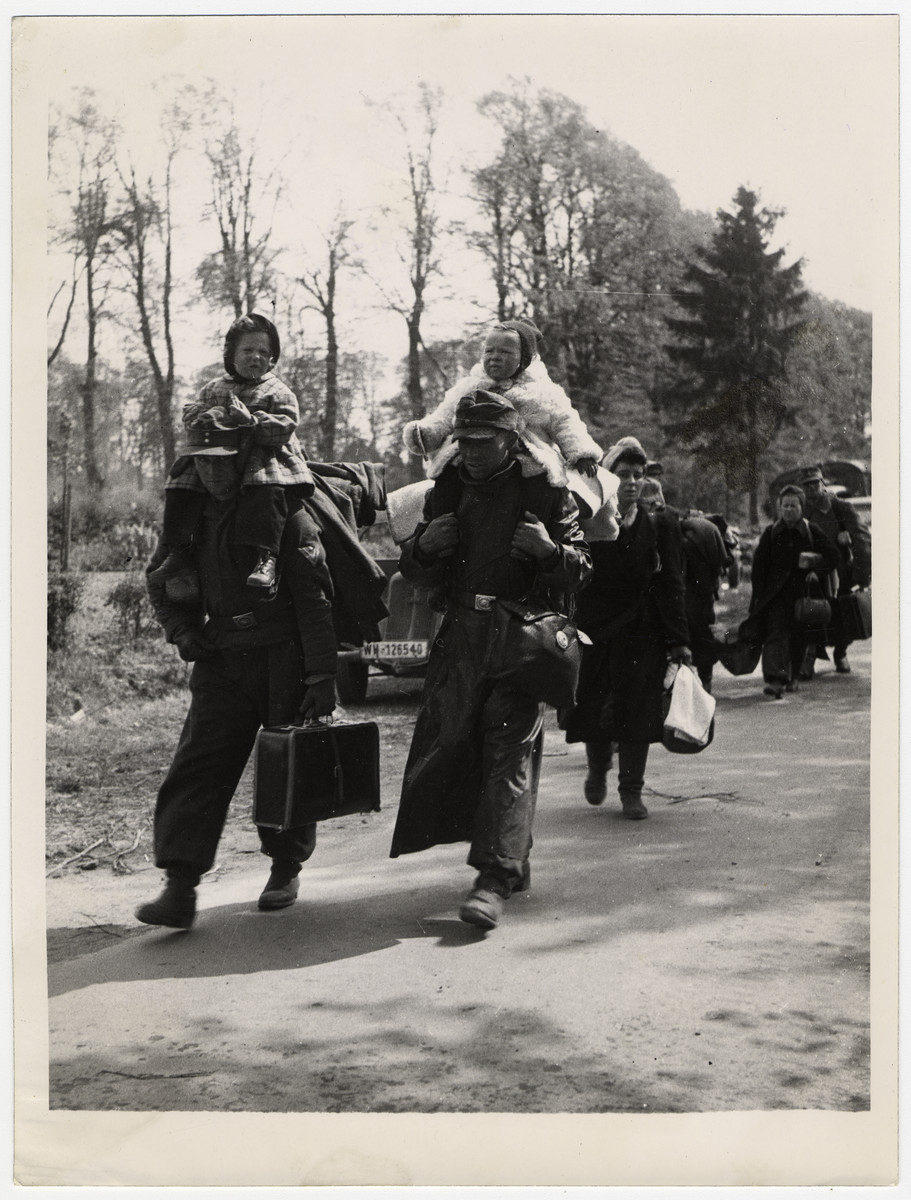 German soldiers and their families surrender to Allied troops.  Original caption reads: Two German soldiers walking to surrender with their children on their shoulders and the rest of their family trailing behind.   German soldiers are giving themselves up to the British in very large numbers. Some are coming into the British lines on every type of vehicle, whilst thousands of others are coming on foot, and bringing their wives and children.