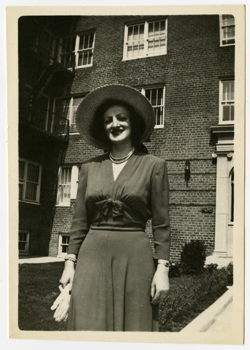 Jewish survivor Sali Bogatyrow poses for a photograph before an unidentified apartment block.