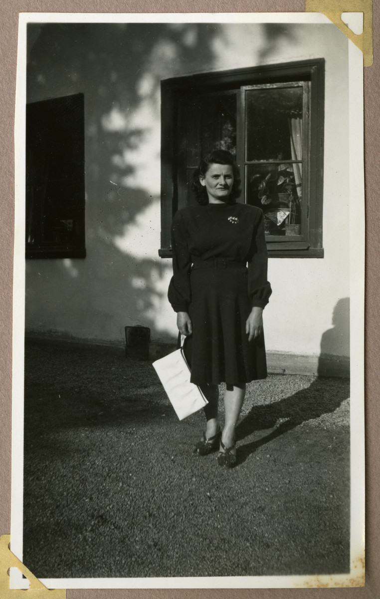 Photograph of a Jewish Holocaust survivor Rose Kahane Leibovic poses otuside a building in Sweden.