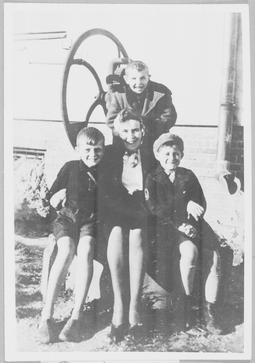 Leopolda Kuropieska poses with three boys during the war.    Her son is on the left, and Itzhack ois on the right wearing a hat.