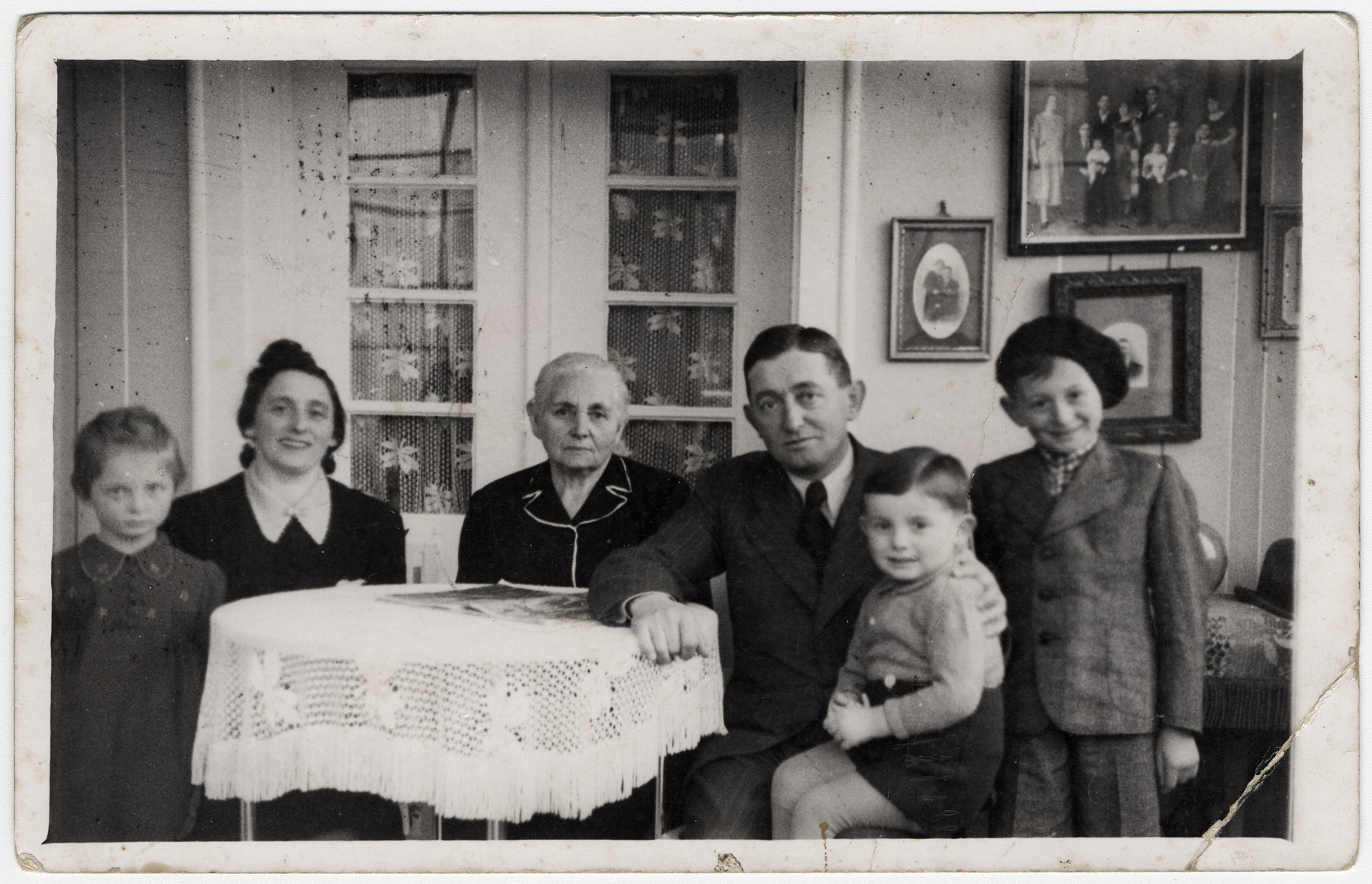 The Brand family sits around a table in their living room.  Pictured from let to right are Agi Brand Etel Brand, Hani Gruenstein, Moshe Brand, Erich Brand and Richard Brand.