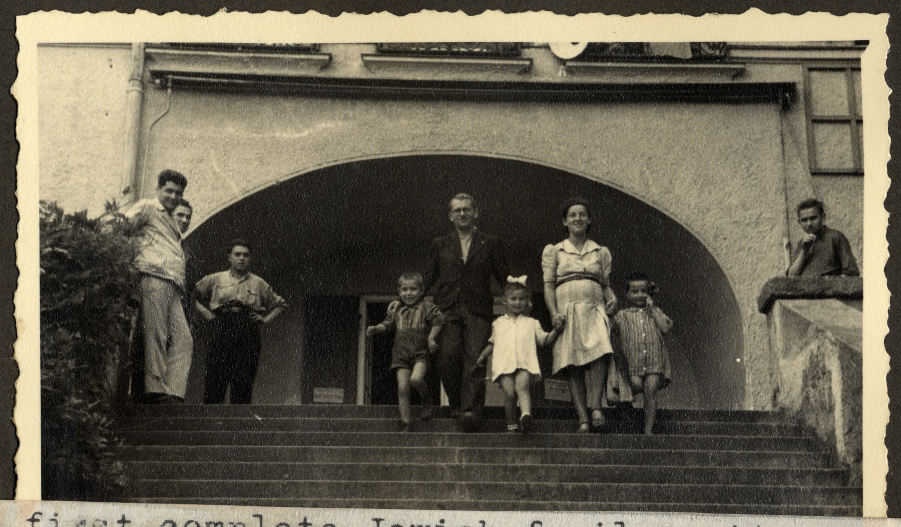 "A reunited Jewish family walks down an exterior  flight of stairs in the Feldafing displaced persons' camp.  The original caption reads: ""The first complete Jewish family unit from Poland.  Parents survived years in concentration camps; their little girl was hidden with Polish peasants, until the parents called for her.  The two boys are orphans, -- only other children at Feldafing."""