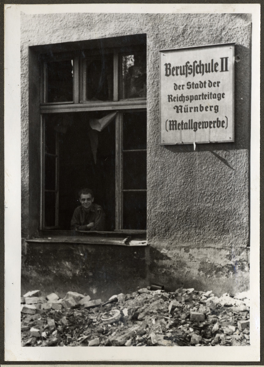 Joseph Eaton poses inside the rubble of what had been the Jewish parochial school in his hometown of Nuremberg.  The sign on the outside of the building says it had been a metal trades school in Nuremberg, the city of [Nazi] Party rallies.