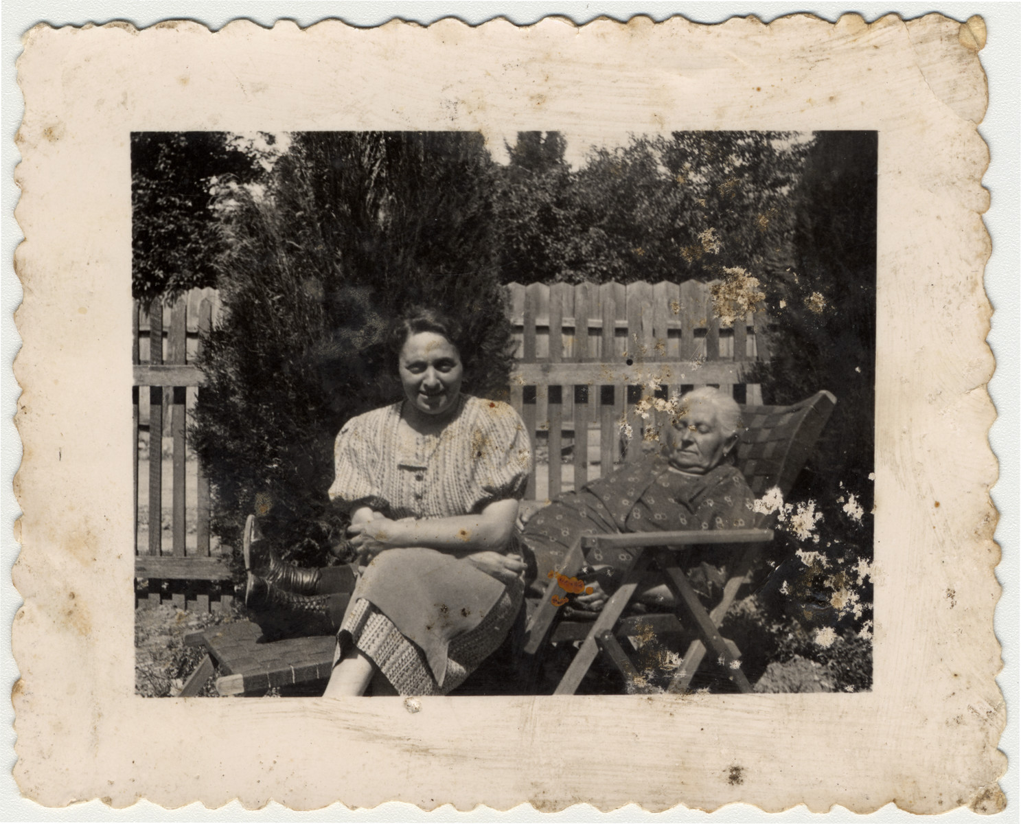 Etel Gruenstein Brand and [probably her mother] sit outside in a sunny garden.