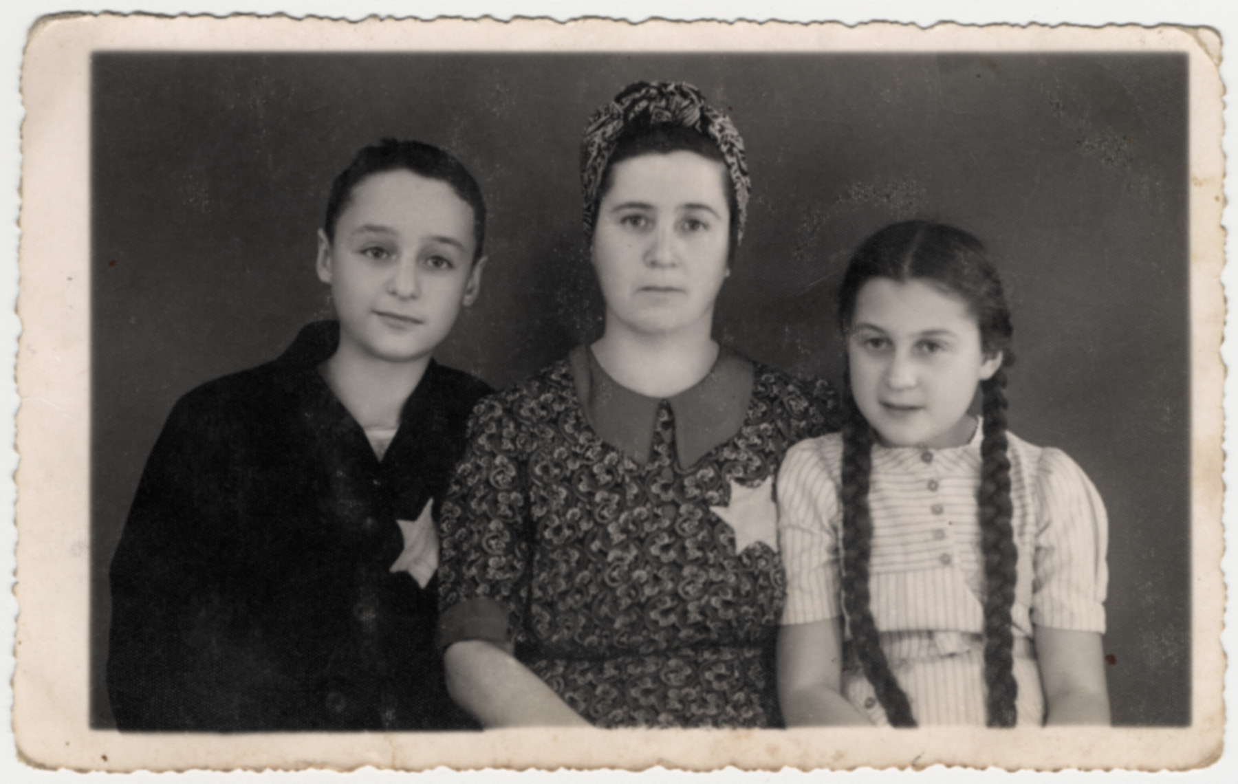 Studio portrait of Martha Loewinger and two of her children wearing yellow stars in the Debrecen ghetto.