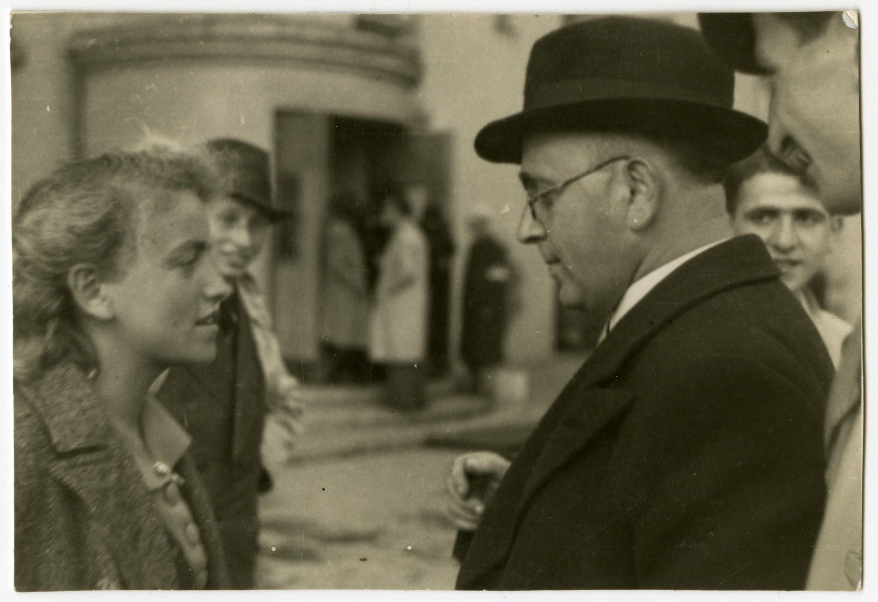 Rosza Grosman (the photographer's sister) talks with Mr. Moskovic in a street of the Lodz ghetto.  Nachman Zonabend looks on at the far right.