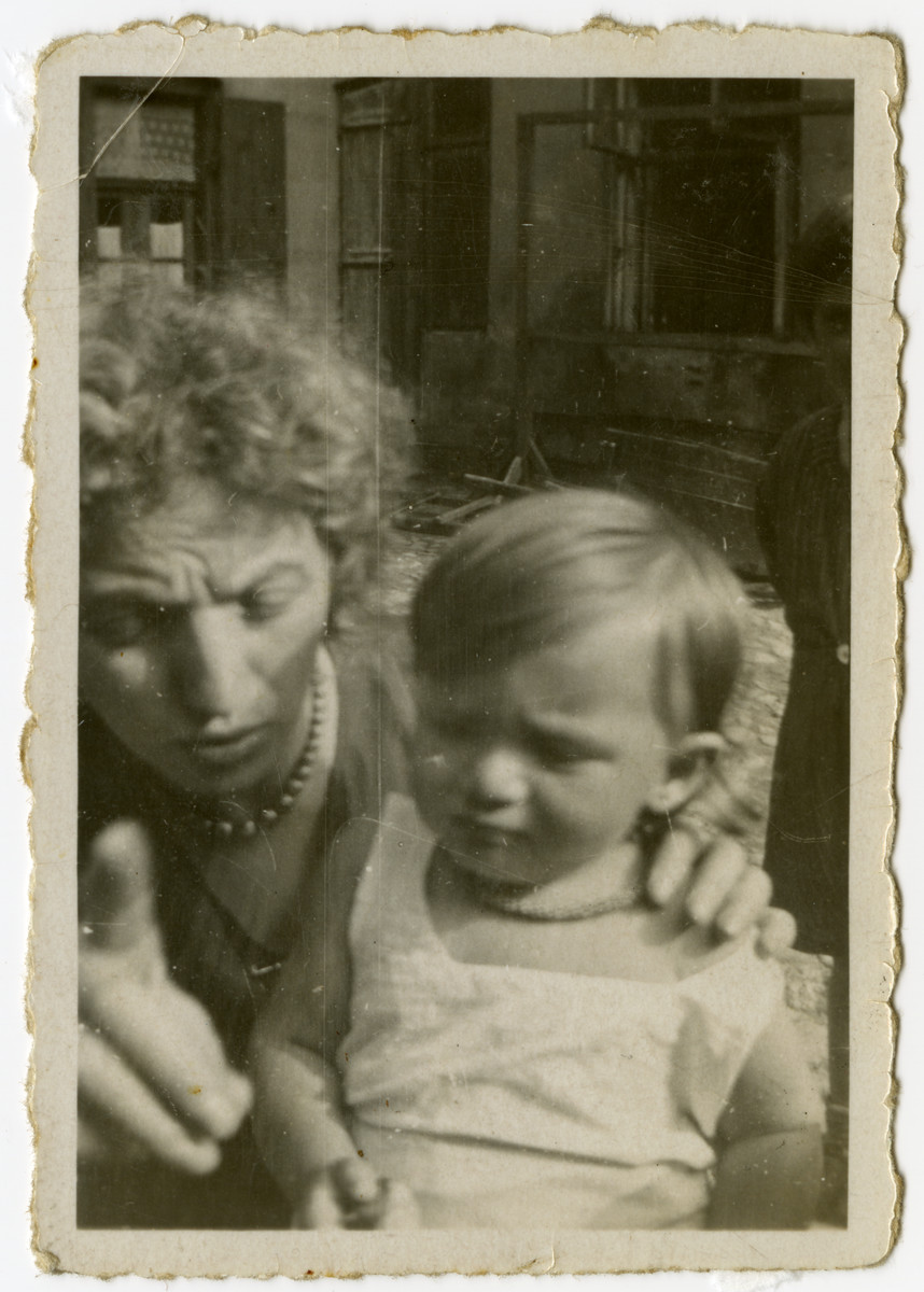 "Close-up portrait of an unidentified woman and child.  The original caption reads ""This is the wife of Chaim Yehoshua and their child.""  [The photograph is undated so it might have been taken in the ghetto.]"