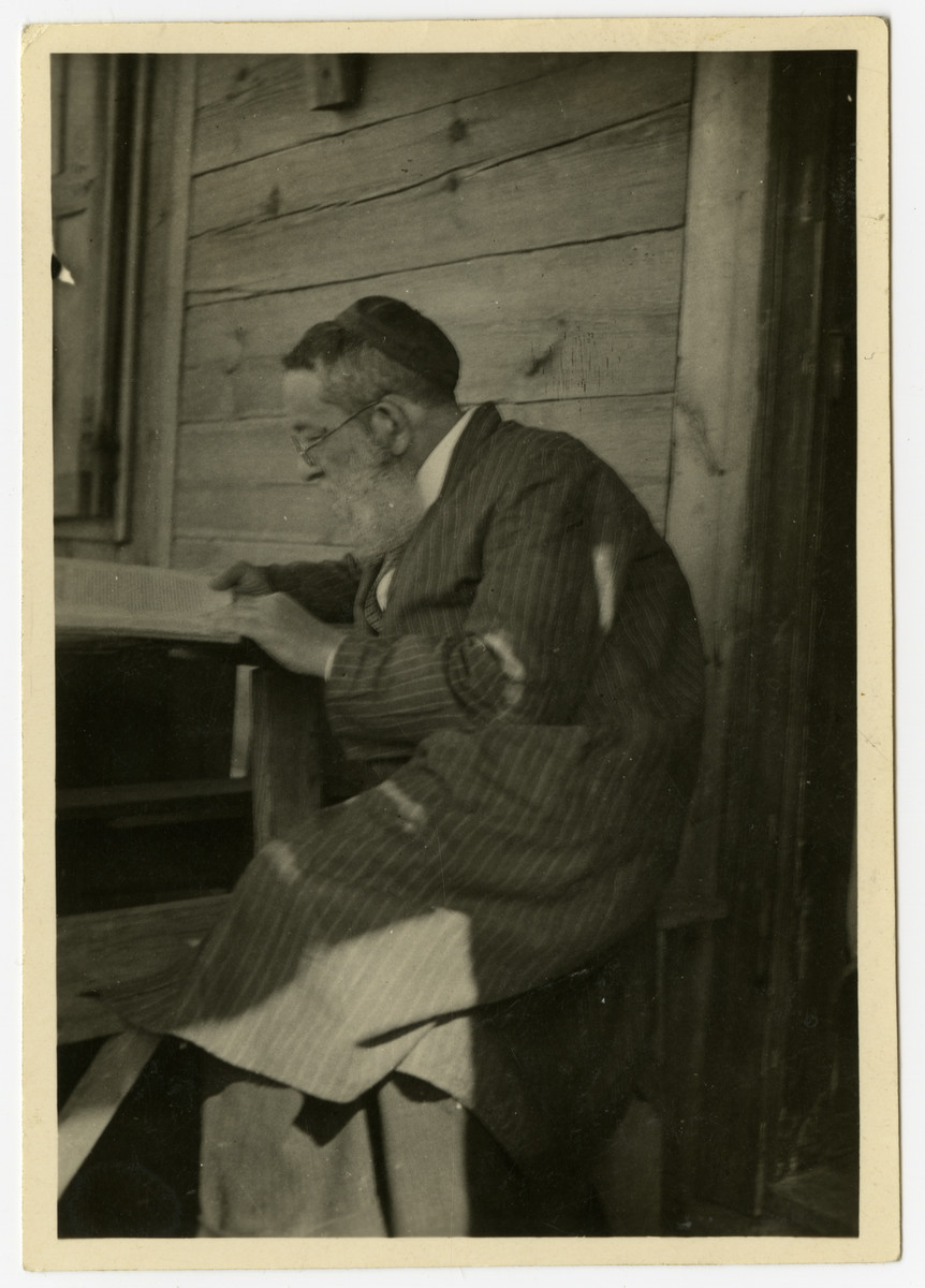 Shmuel Dawid Grosman (father of Mendel) sits outside his vacation cottage and studies a religious text.