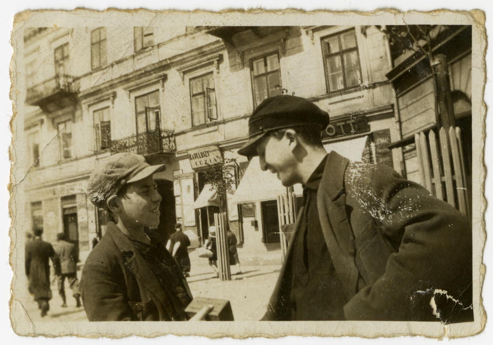 Mendel Grosman (right) talks to a friend on a street in Lodz.