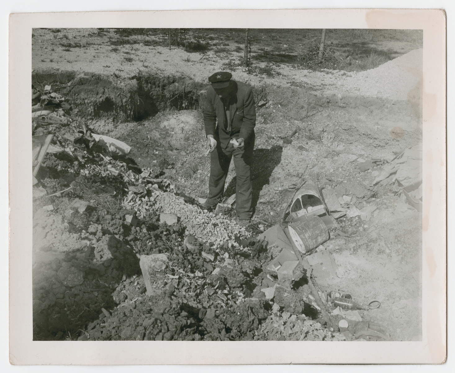 A Yugoslav survivors examines what is possibly a mass grave in the Dachau concentration camp.