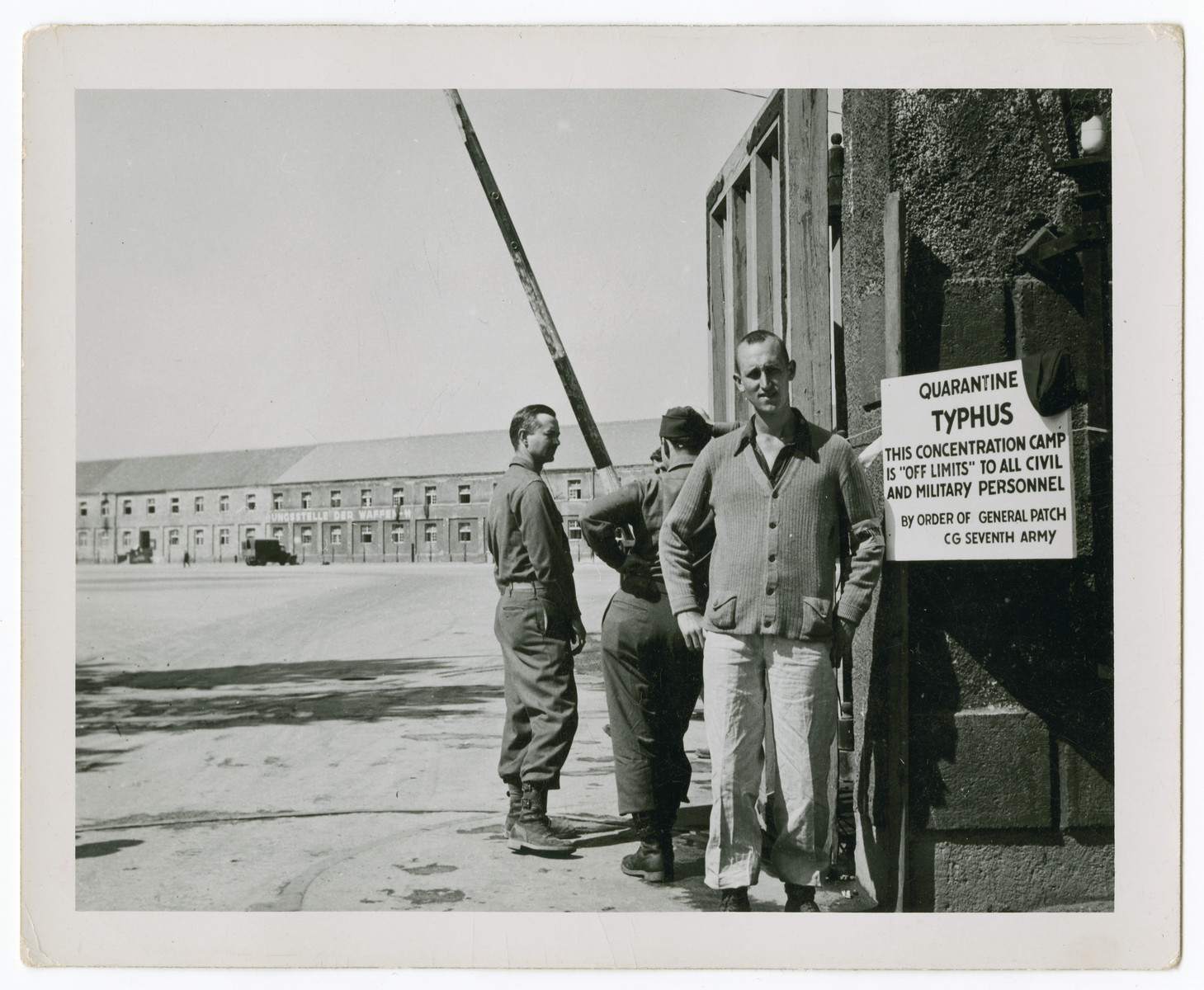 American military personnel and a liberated prisoner stand by a quarantine sign near the entrance of the Dachau concentration camp.