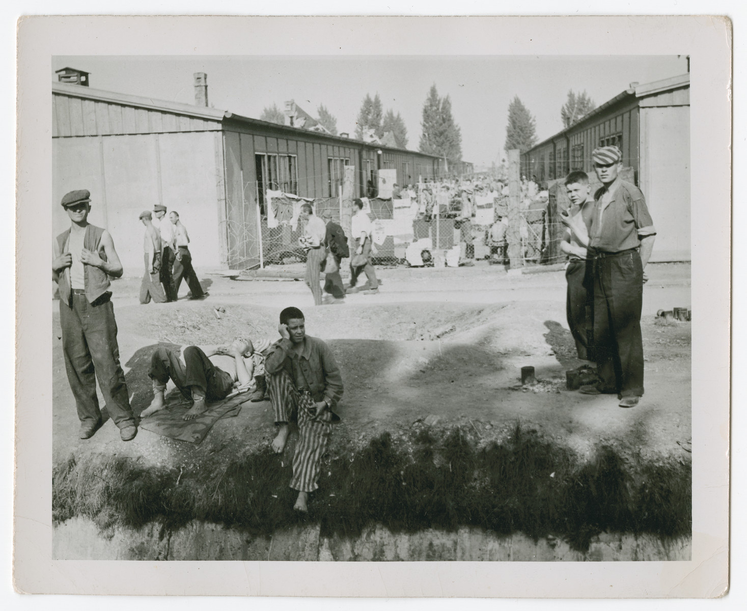 Survivors gather and relax on the grounds of the Dachau concentration camp after liberation.