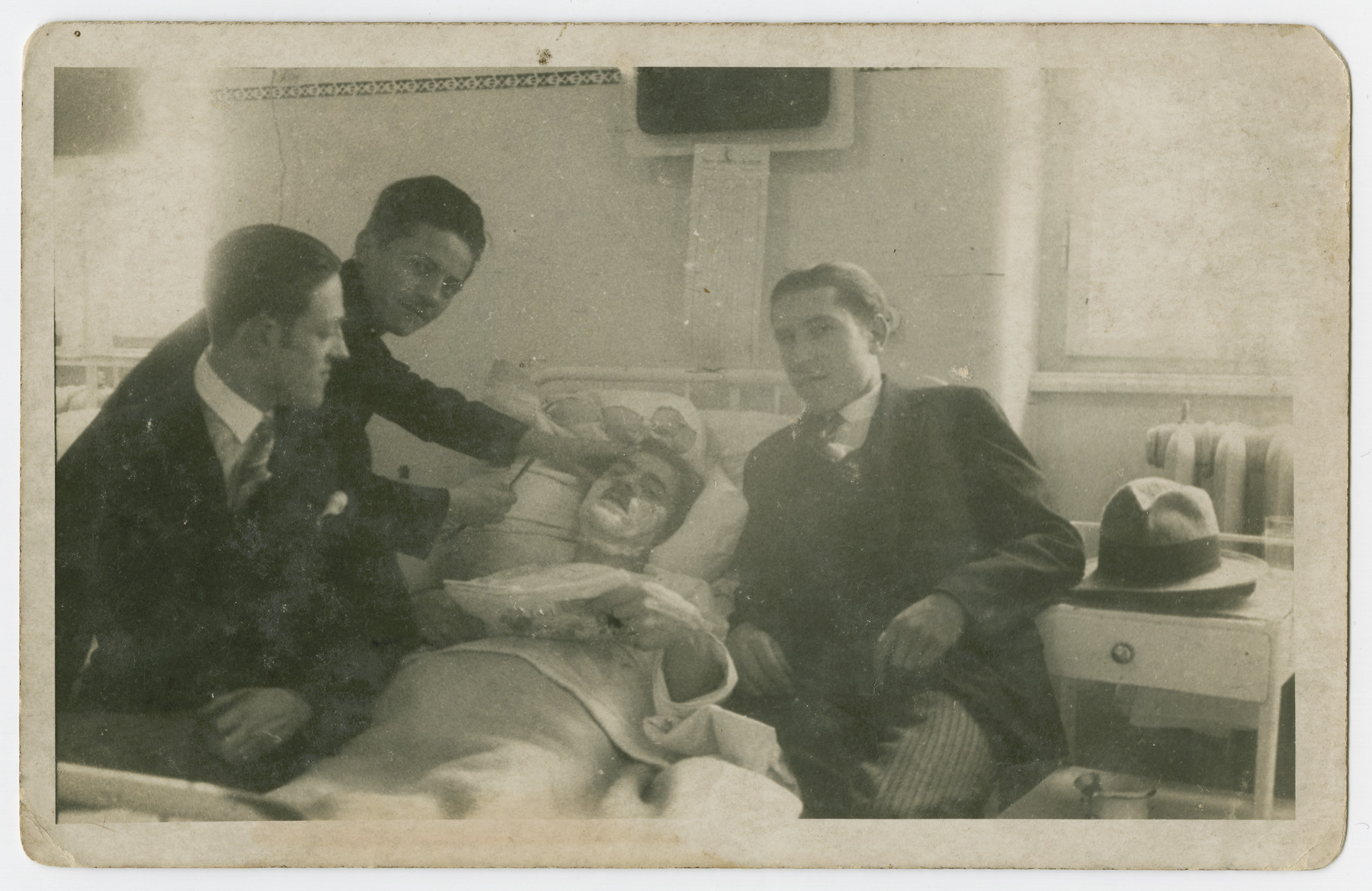 Adolf Lebovics (first man on the left ) and a group of friends visit and shave the face of a hospitalized friend.
