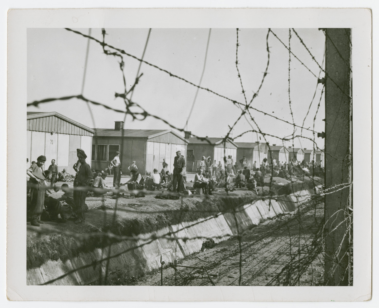 Survivors gather next to the moat of the Dachau concentration camp.